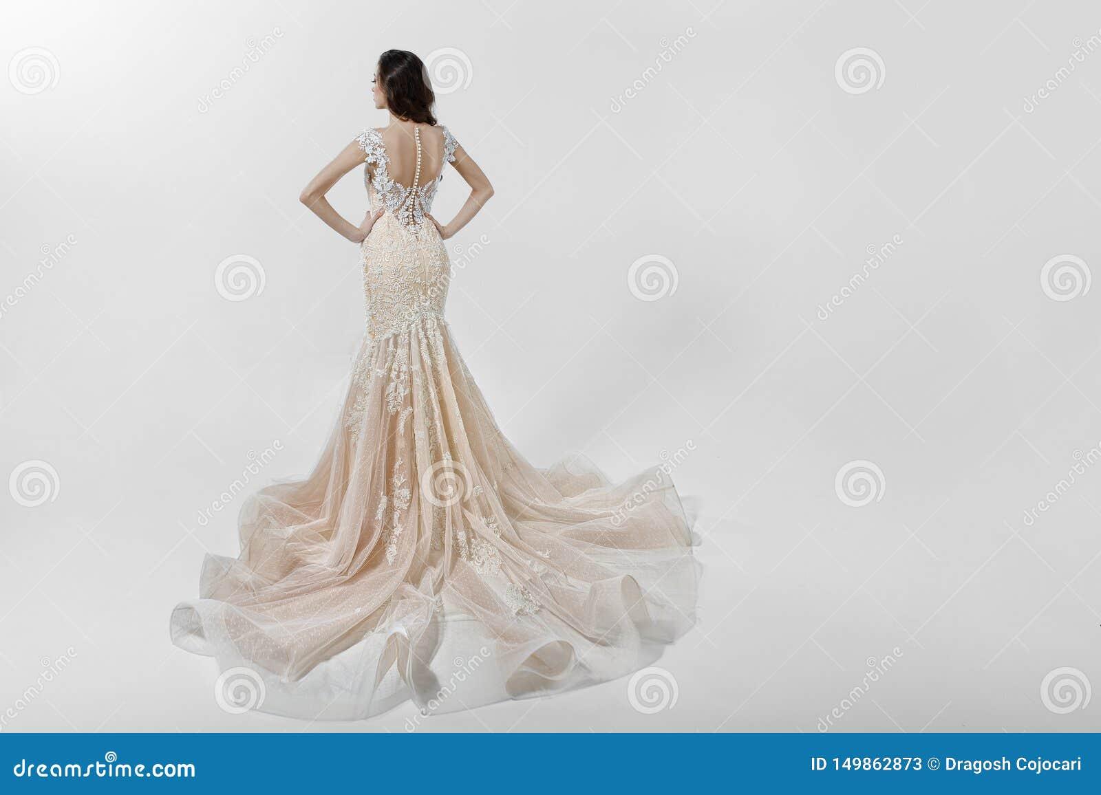 Schönes Mädchen, das mit der Rückseite, gekleidet in einem Heiratskleid mit der Stickerei, lokalisiert auf einem weißen Hintergru