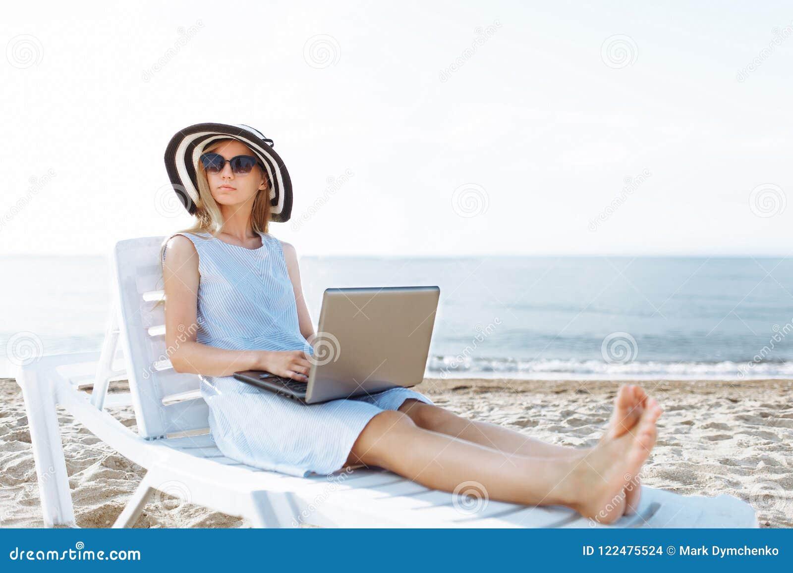 Schönes Mädchen, das mit einem Laptop auf einem Liege, eine Frau im Urlaub arbeitet, Jobsuche sitzt
