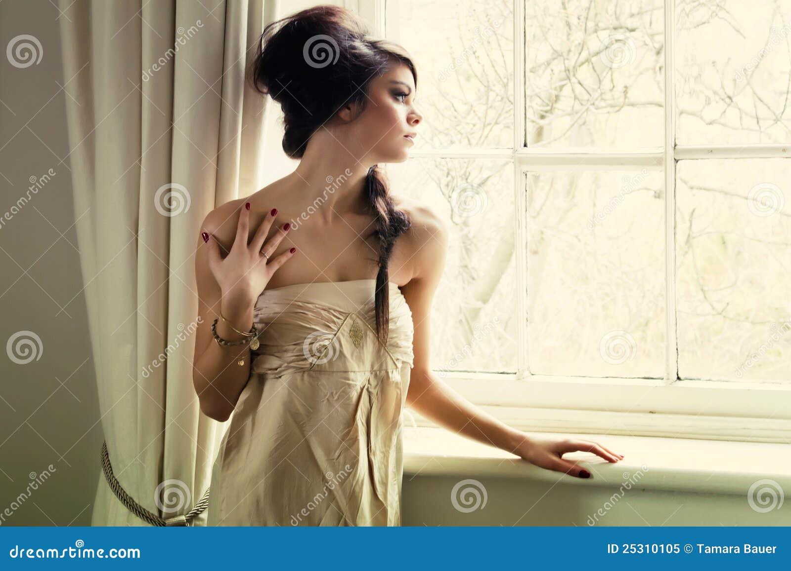 Schönes Mädchen durch Fenster