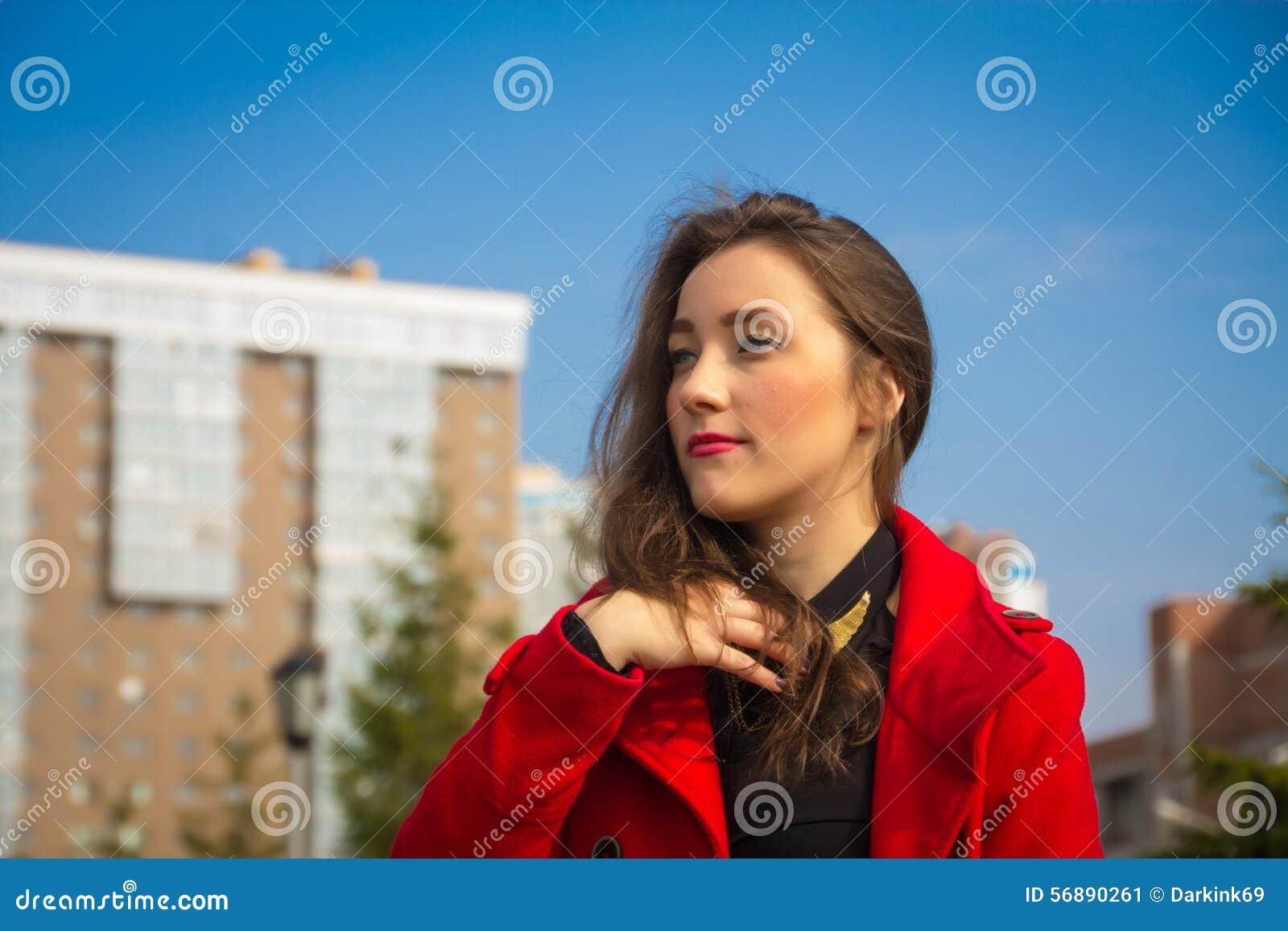Schönes Mädchen in einem roten Mantel auf einem Hintergrund von Häusern