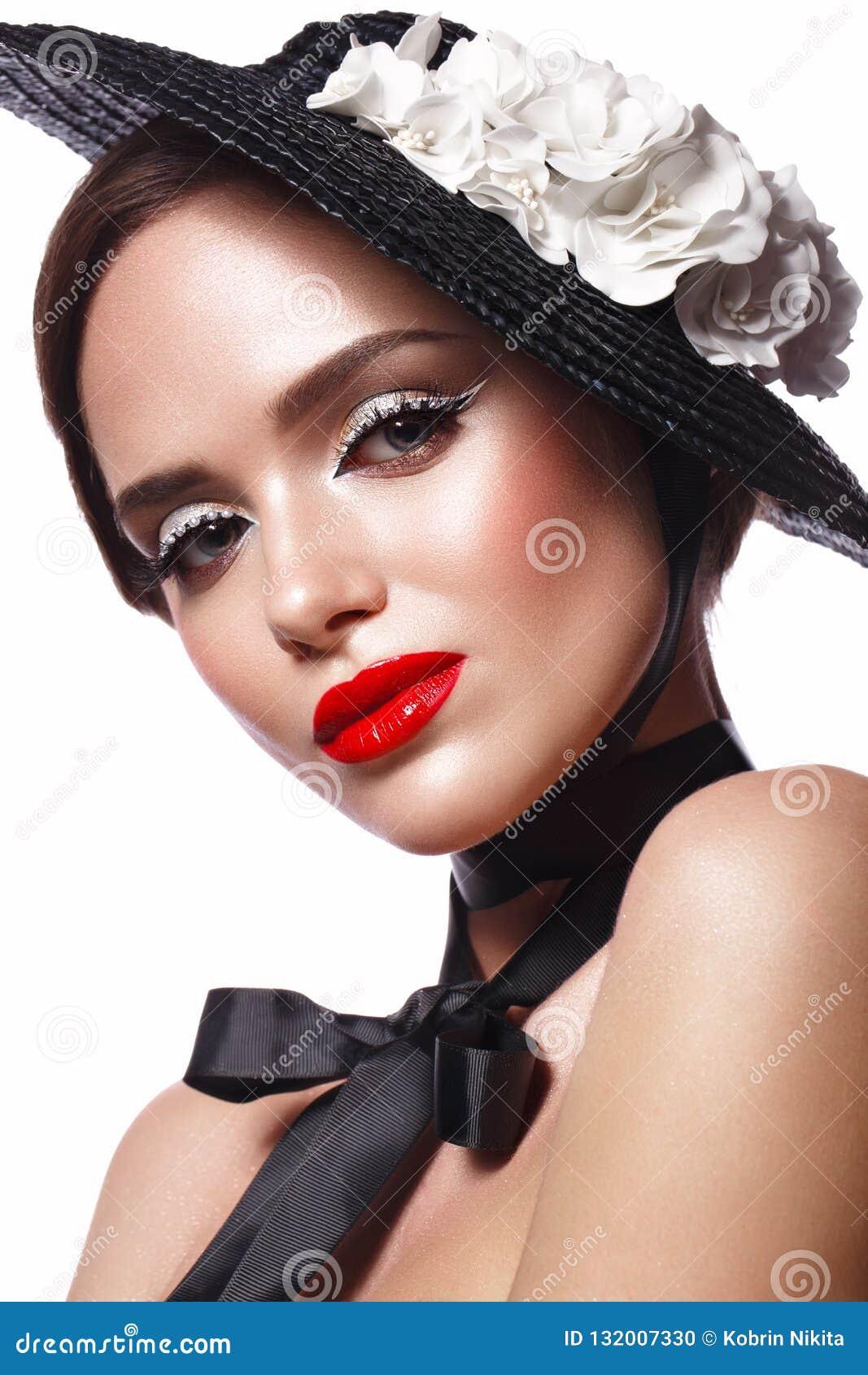 Schönes Mädchen in einem schwarzen Hut mit Blumen und Retro- Make-up Schönes lächelndes Mädchen