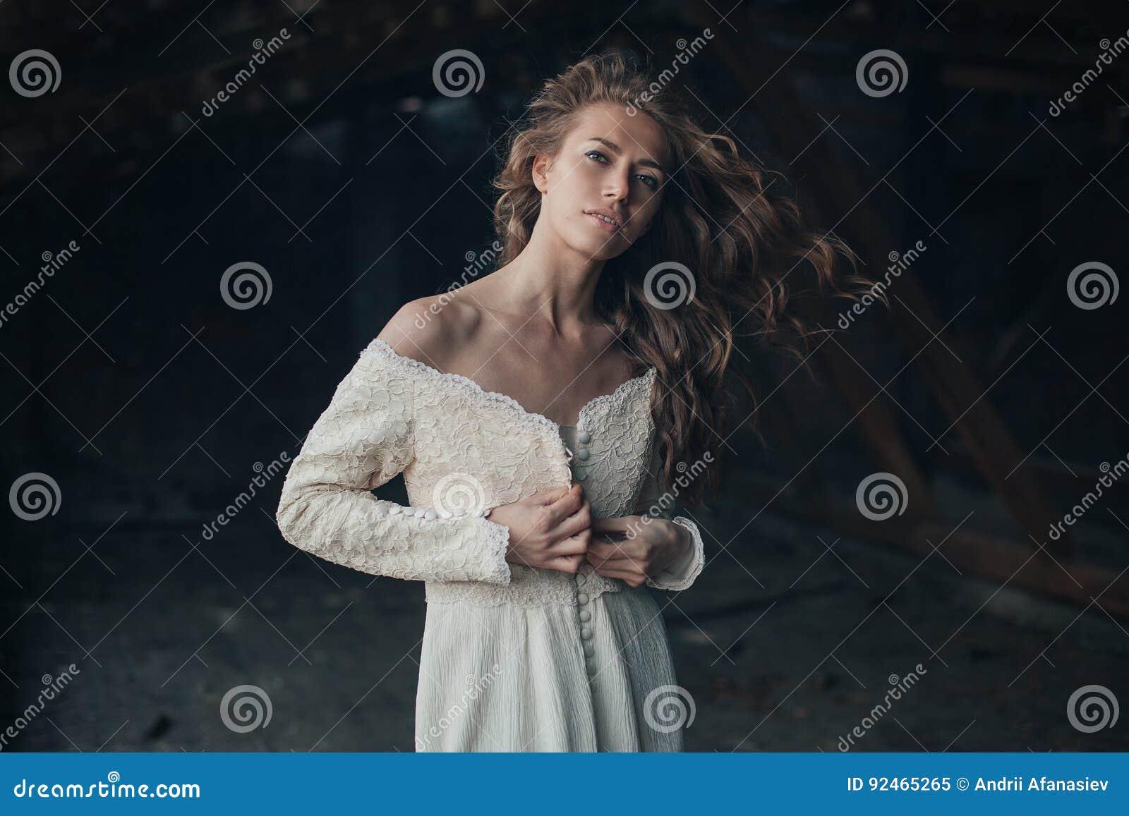 Schönes Mädchen herein im weißen Weinlesekleid mit dem gelockten Haar, das auf dem Dachboden aufwirft Frau im Retro- Kleid Besorg