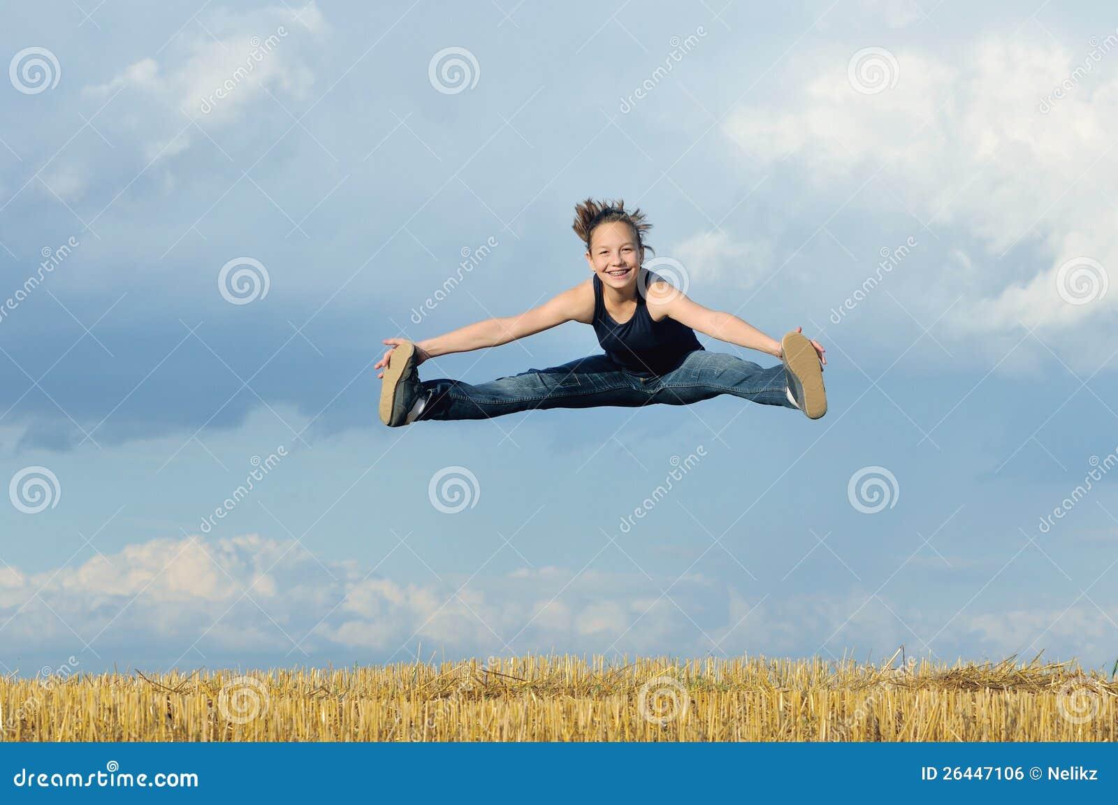Schönes Mädchen im gymnastischen Sprung gegen blauen Himmel