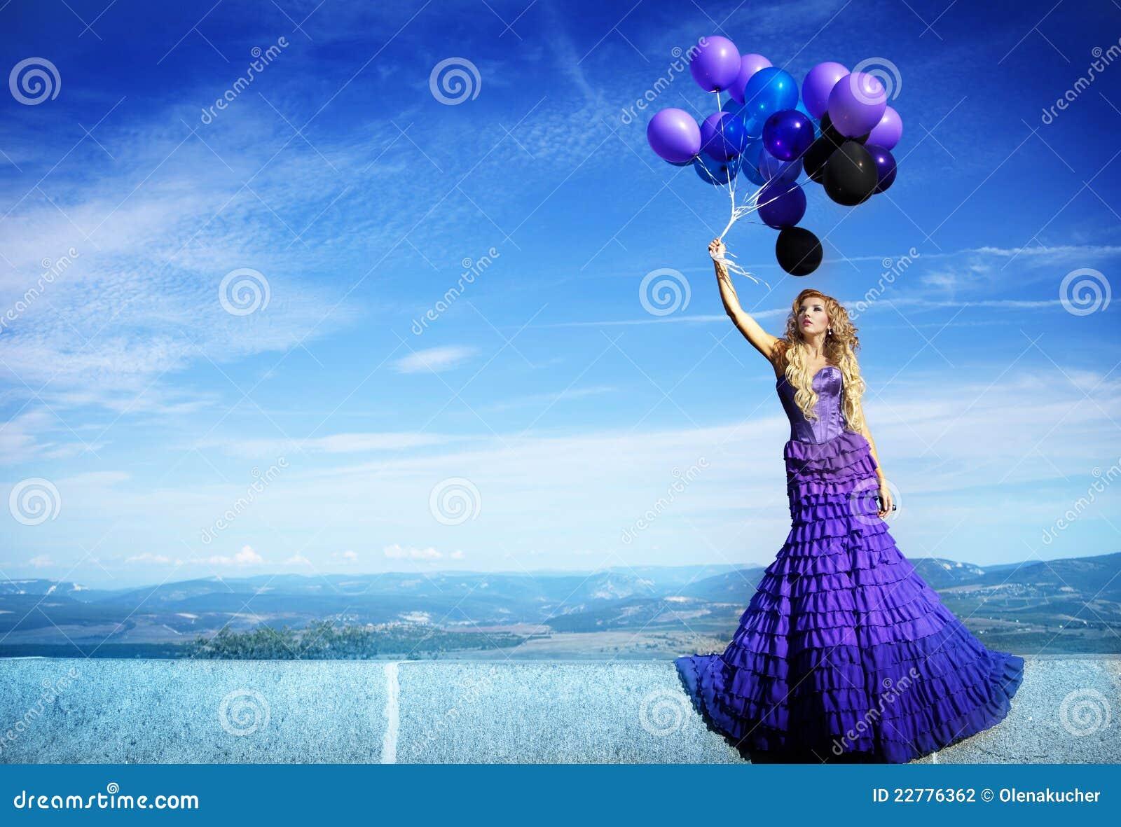 Schönes Mädchen im purpurroten Kleid mit Ballonen