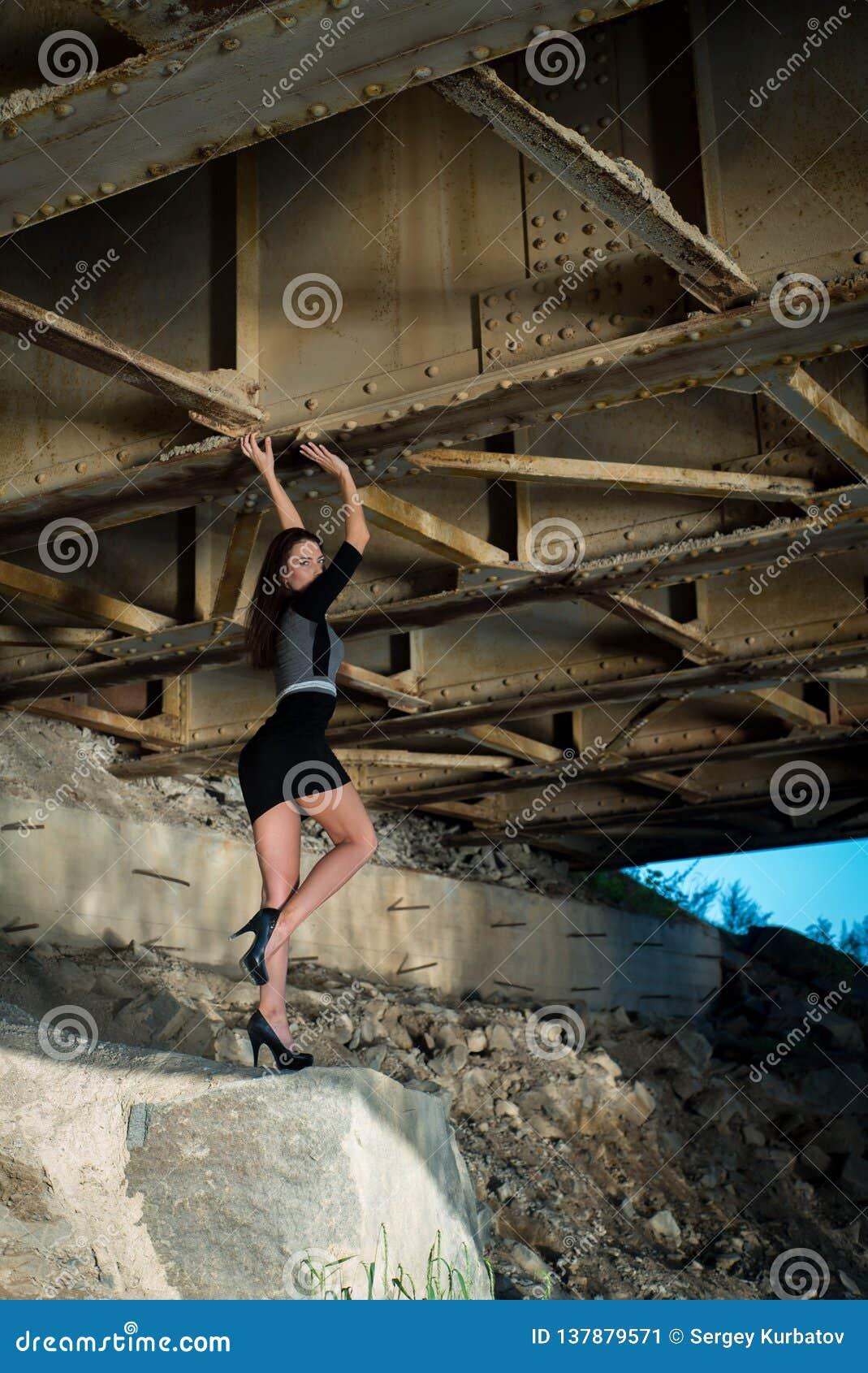 Schönes Mädchen im Rock unter der Brücke