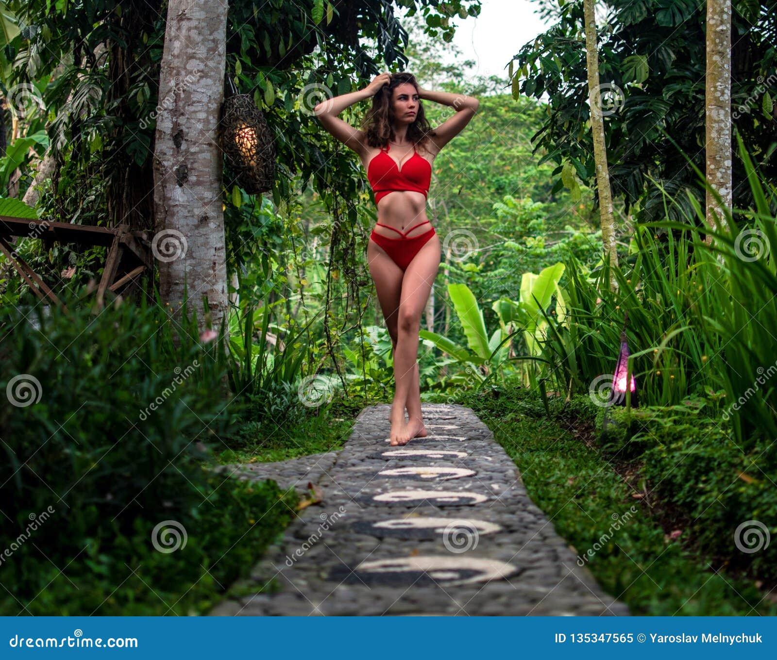 Schönes Mädchen im roten Badeanzug, der im tropischen Standort mit grünen Bäumen aufwirft Junger Sport modelliert im Bikini mit p
