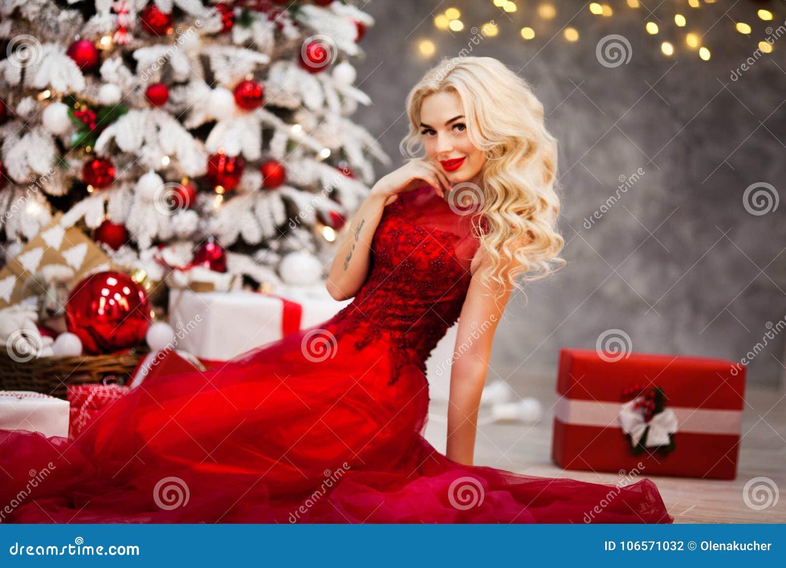 schönes mädchen im roten kleid, trifft weihnachten am baum