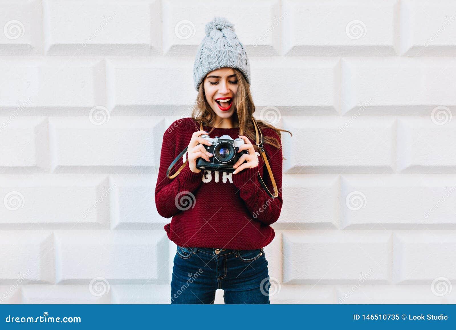 Schönes Mädchen in marsala Strickjacke auf grauem Wandhintergrund Sie trägt Strickmütze, wird erstaunt Kamera herein betrachtend