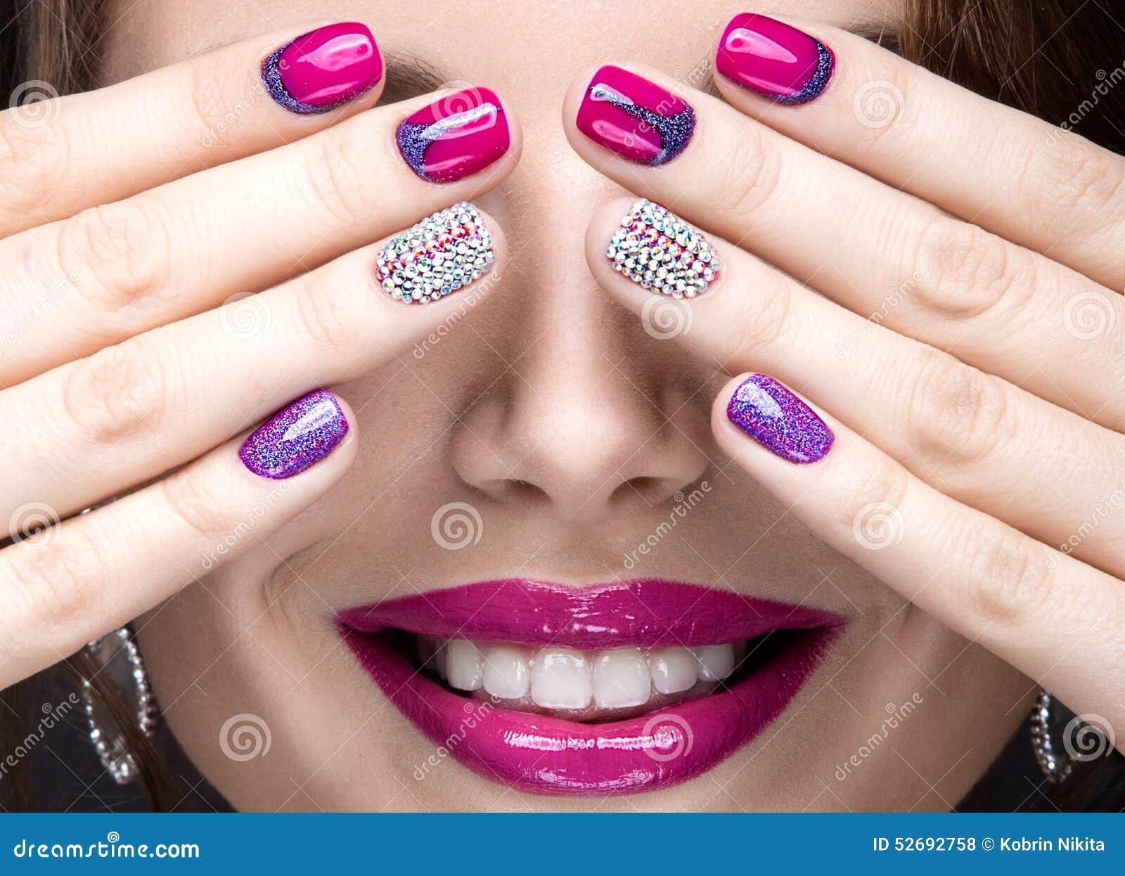 Schönes Mädchen mit einem hellen Abendmake-up und rosa Maniküre mit Bergkristallen Nageldesign Schönes lächelndes Mädchen