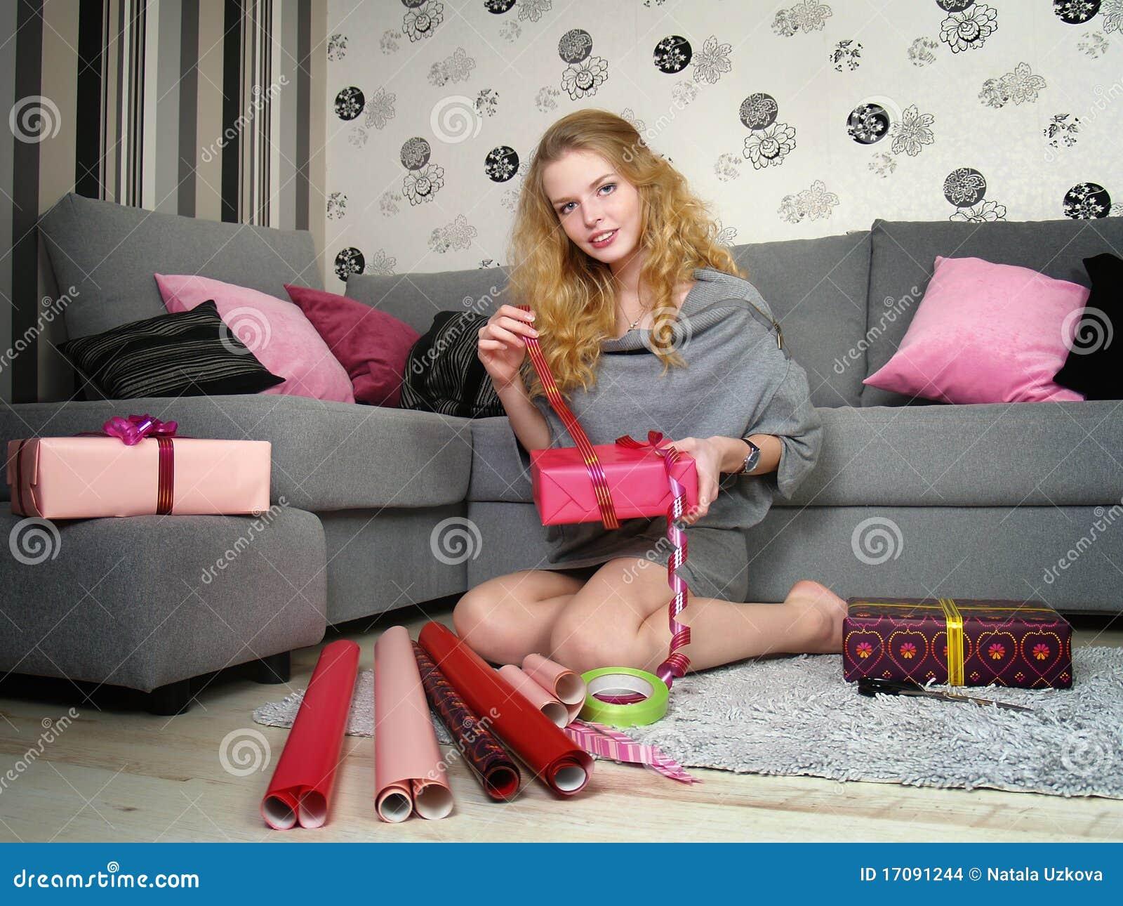 Schönes Mädchen packt Geschenke für einen Feiertag