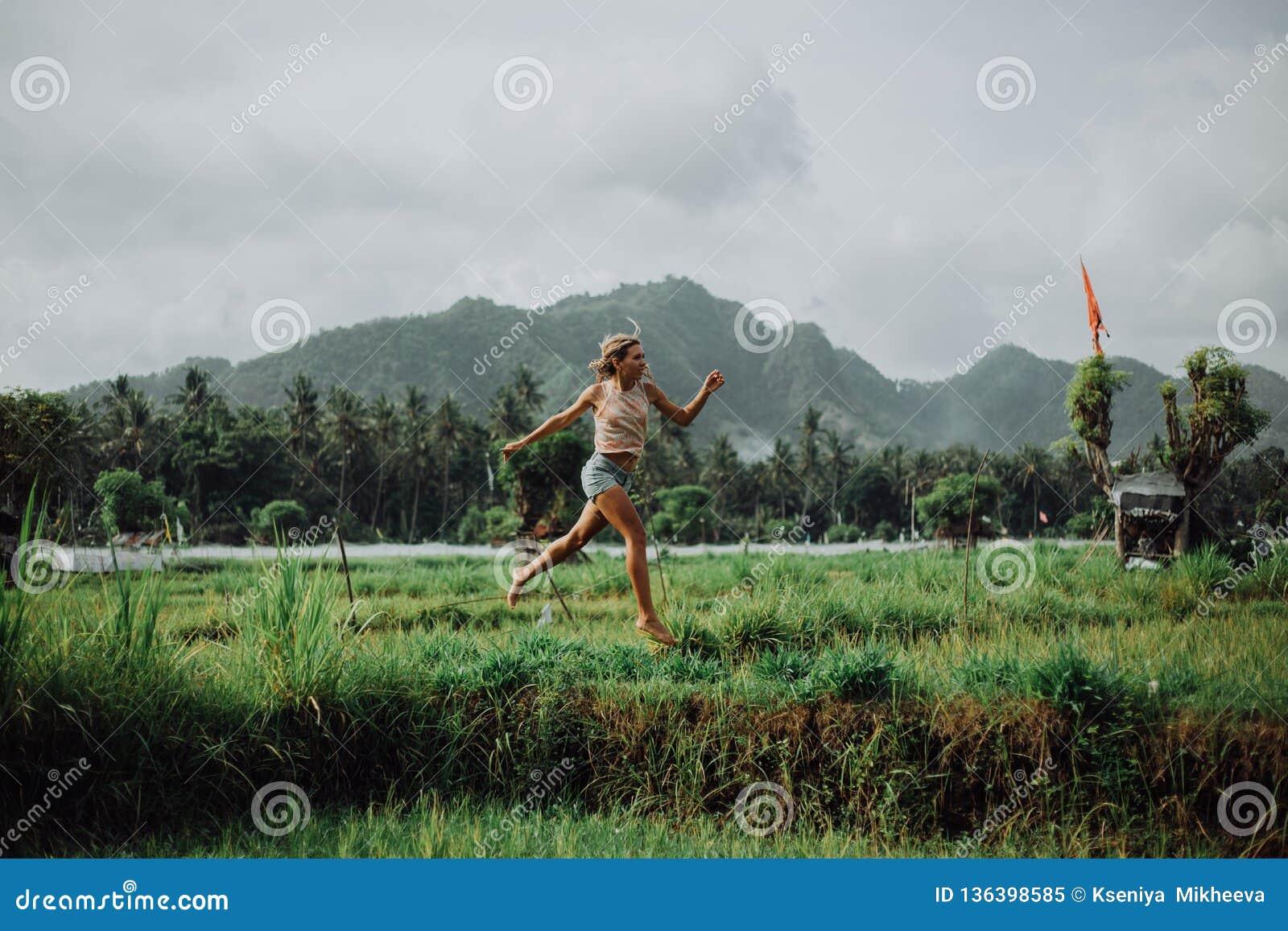 Schönes Mädchen springen, die unglaublichen Reisfelder, ein Vulkan im Hintergrund und die Berge Kühler Hintergrund glücklich