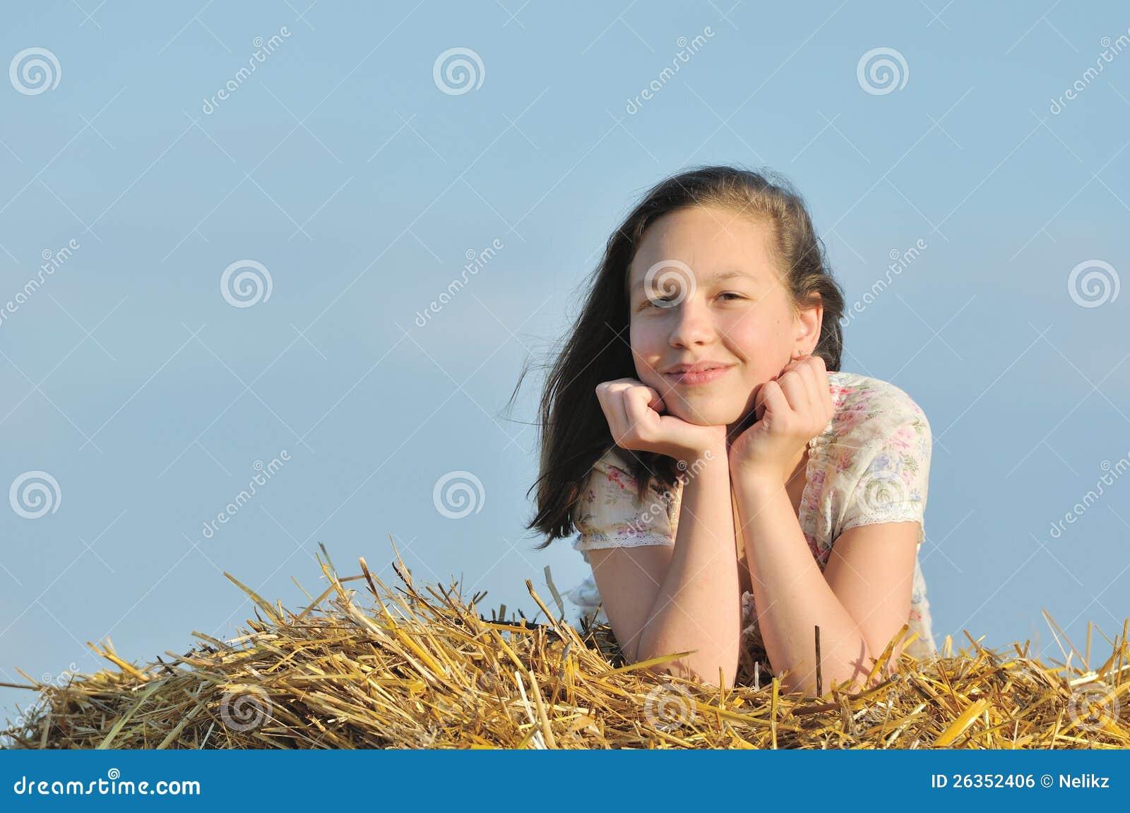 Schönes Mädchen, welches die Natur im Heu genießt