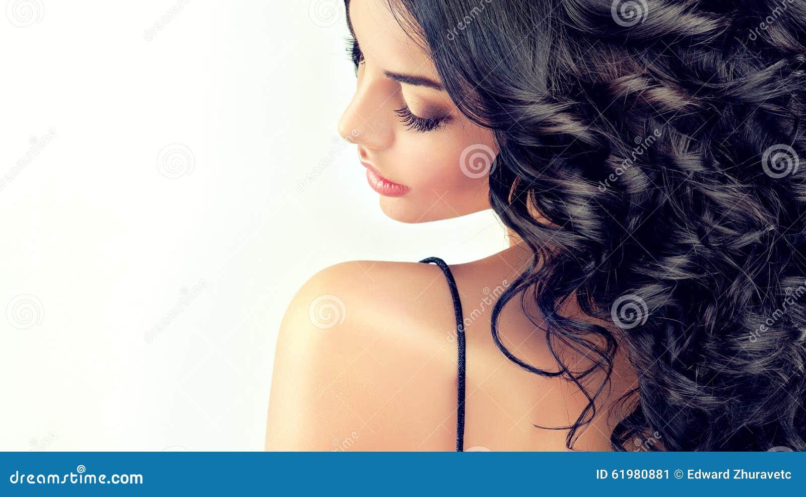 Schönes Mädchenmodell des Porträts mit dem langen schwarzen Kraushaar