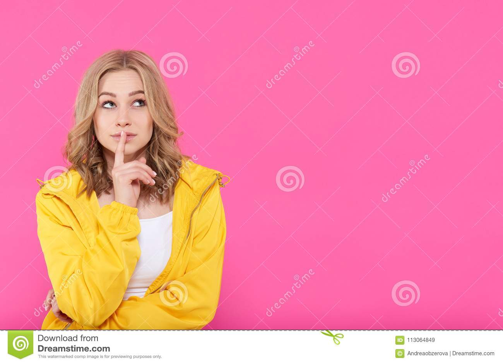 Schönes modisches Mädchen in der bunten Kleidung tief in den Gedanken, oben schauend mit dem Finger auf Lippen Attraktives Porträ