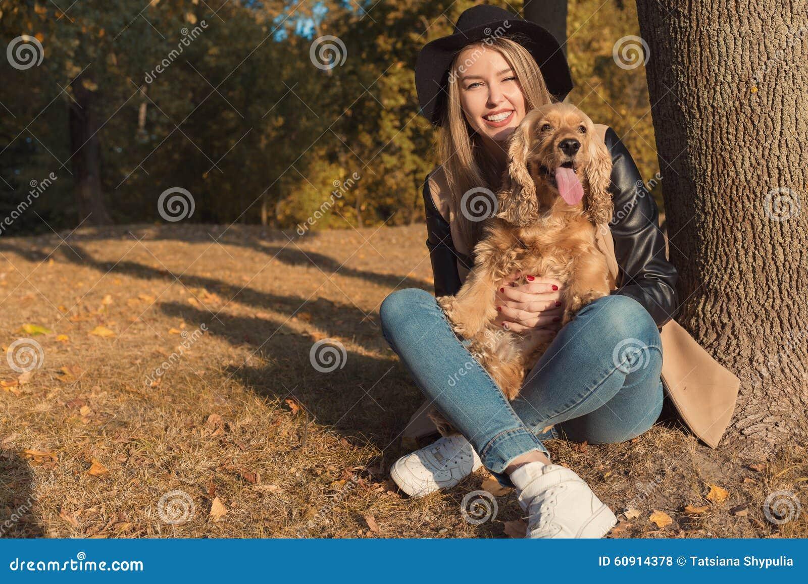 Schönes nettes glückliches Mädchen in einem schwarzen Hut, der mit ihrem Hund in einem Park im Herbst ein anderer sonniger Tag sp