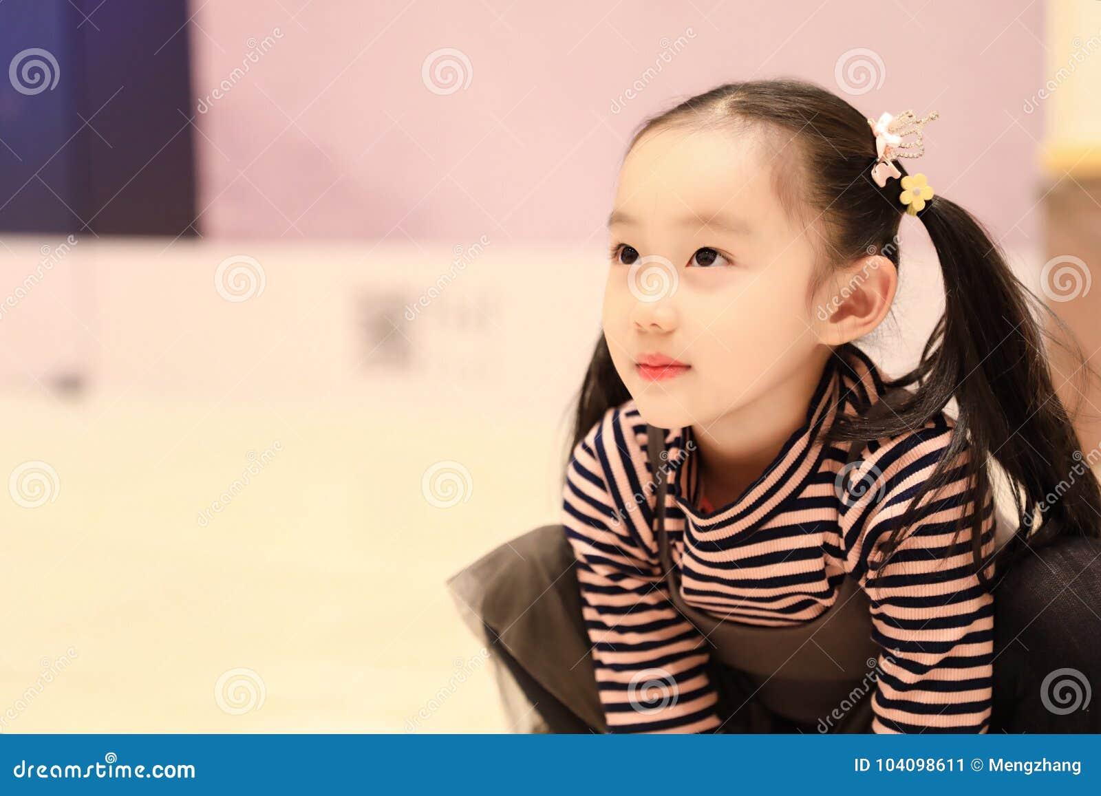 Schönes nettes kleines Mädchen, das Vergnügensboden auf Spielplatz spielt
