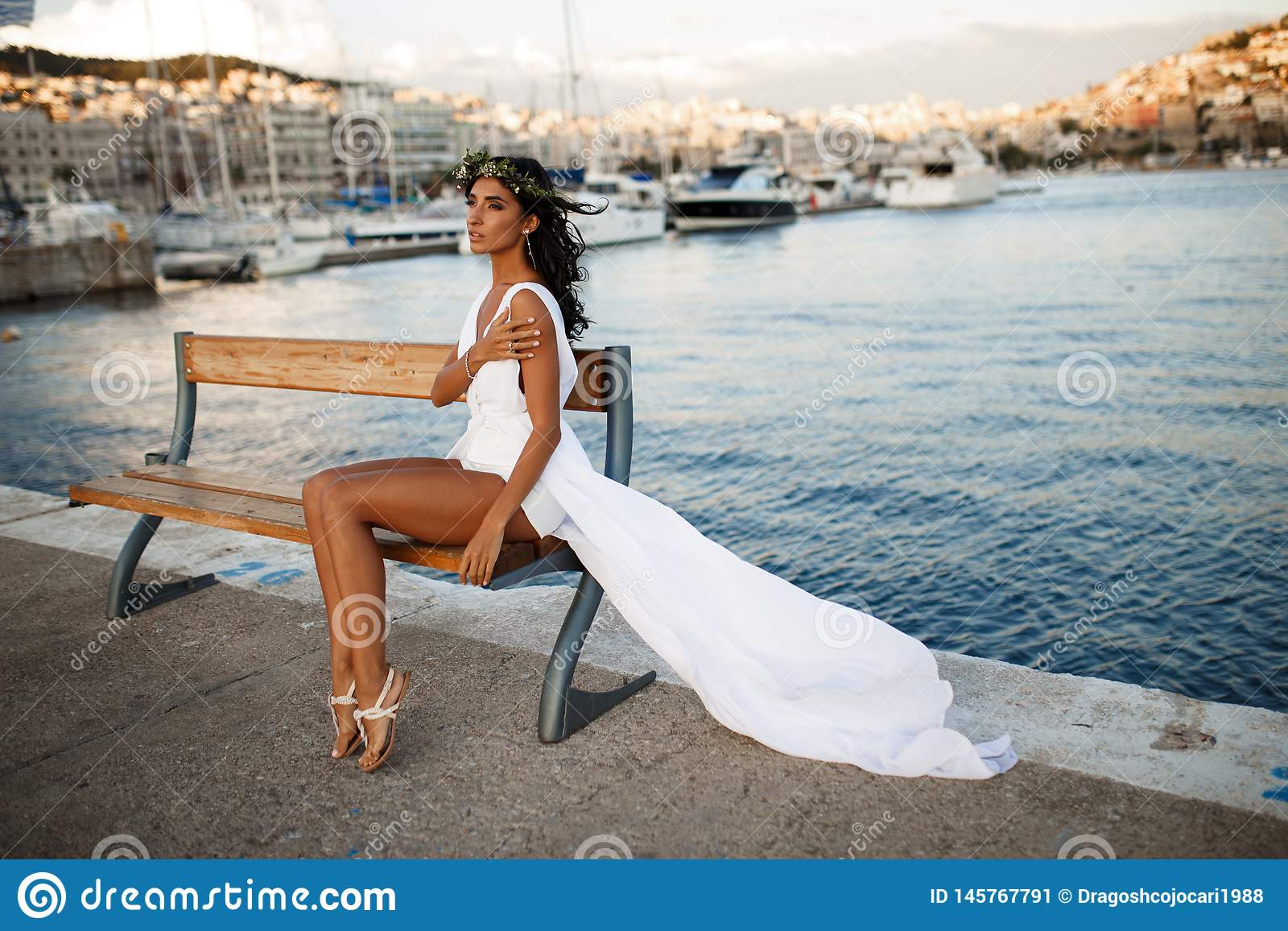 Schönes Porträt einer brunette jungen Frau wirft sinnliches im weißen Kleid auf Bank, hinter Mittelmeer in Griechenland auf