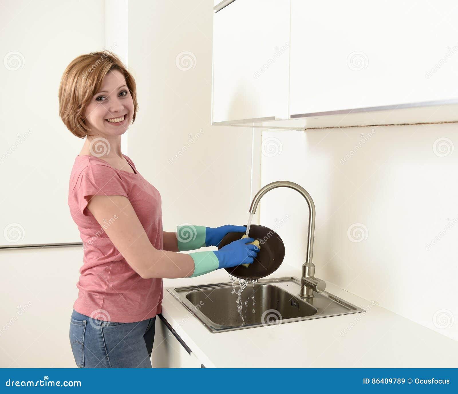 Schönes rotes Haarfrauenlächeln glücklich und Positiv, das die Teller am Spülbecken wäscht
