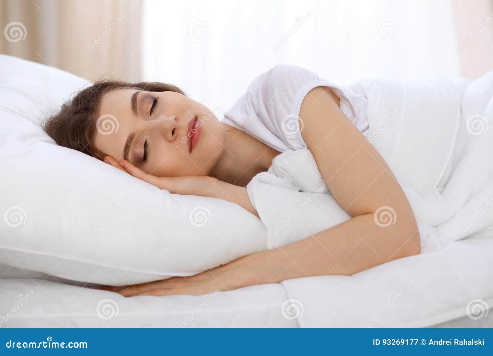 Schönes Schlafenim Bett morgens liegen der jungen Frau und sich entspannen Sonniger Tagesanfänge ist- die Zeit, eine Arbeit anzus