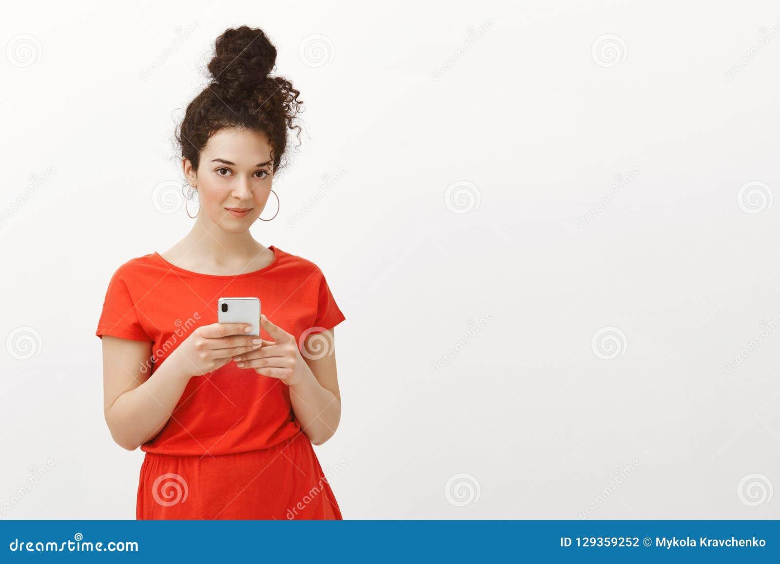 Schönes stilvolles weibliches Mädchen mit dem gelockten Haar gekämmt im Brötchen im roten Kleid, Smartphone halten und starren Ka