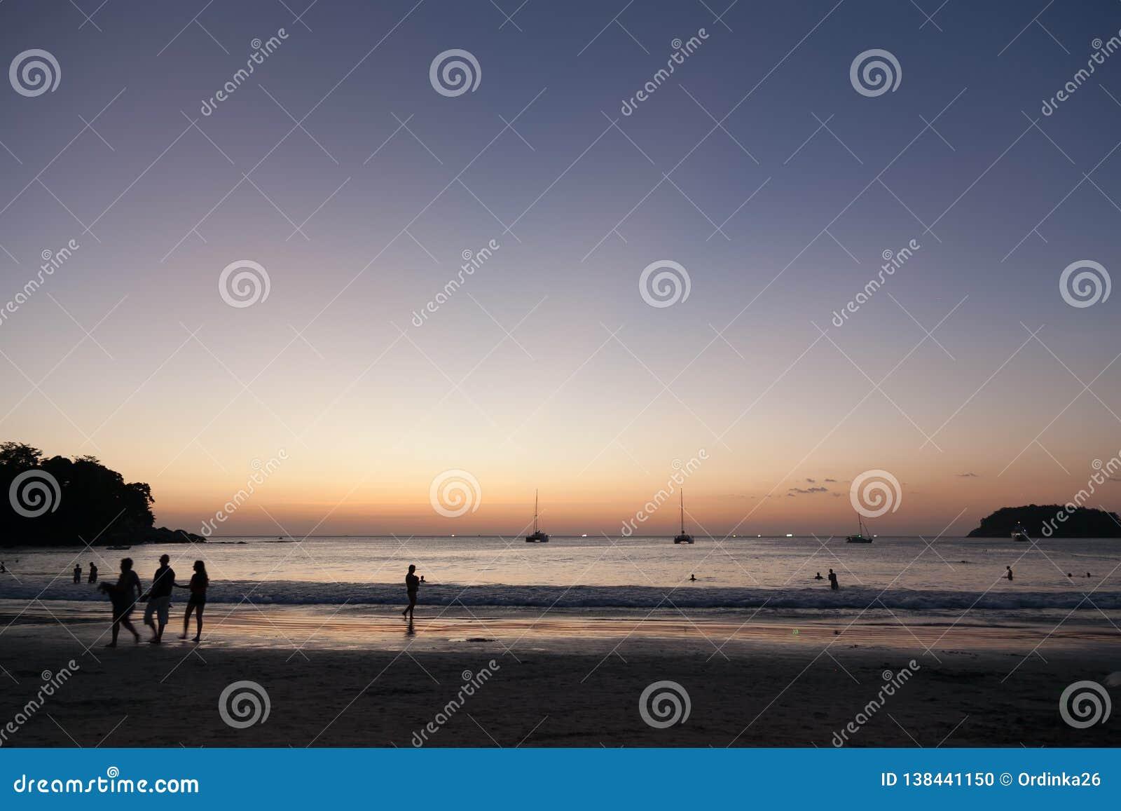 Schönes Strand kata Phuket in Thailand auf puhket Insel Schattenbilder von Leuten bei Sonnenuntergang Im Vordergrund sind das Sch