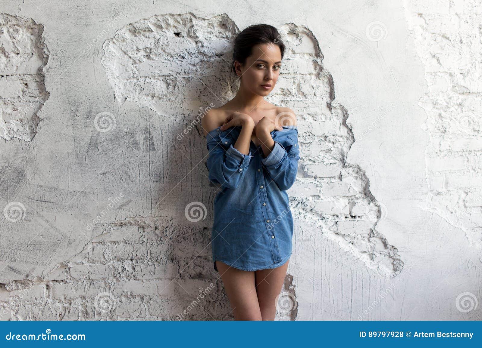Schönes und dünnes Brunettemädchen im blauen Denimhemd ist an der weißen Backsteinmauer