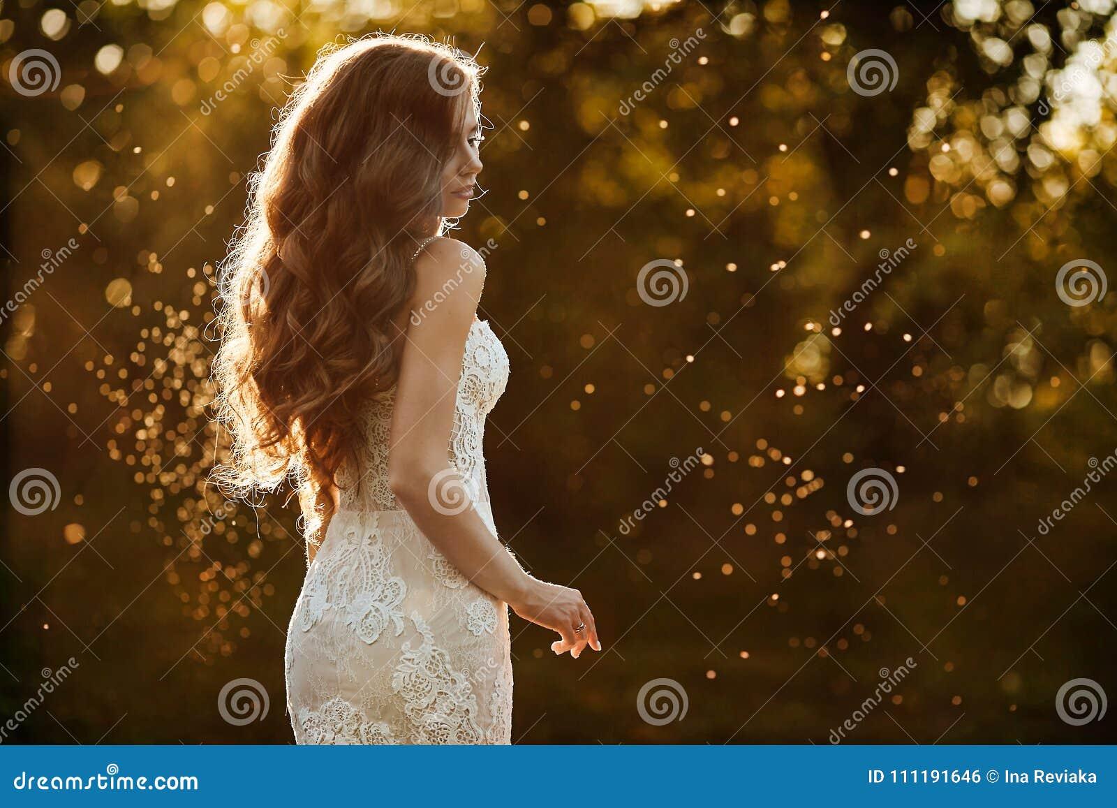Schönes und junges Brunettemodellmädchen, im weißen Spitzekleid, steht mit ihr zurück am Park bei dem Sonnenuntergang