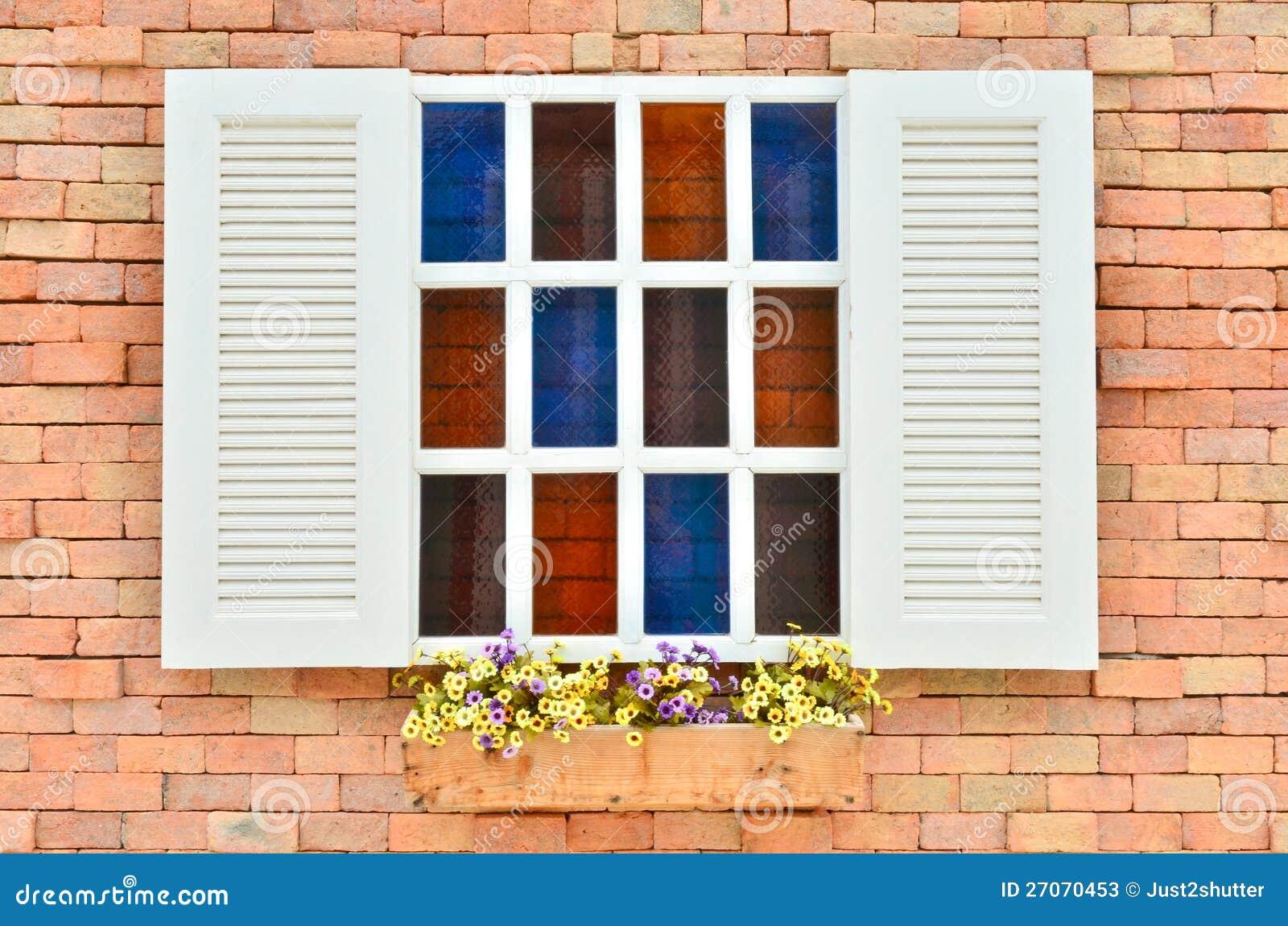 Schönes weißes hölzernes Fenster mit bunter Blume