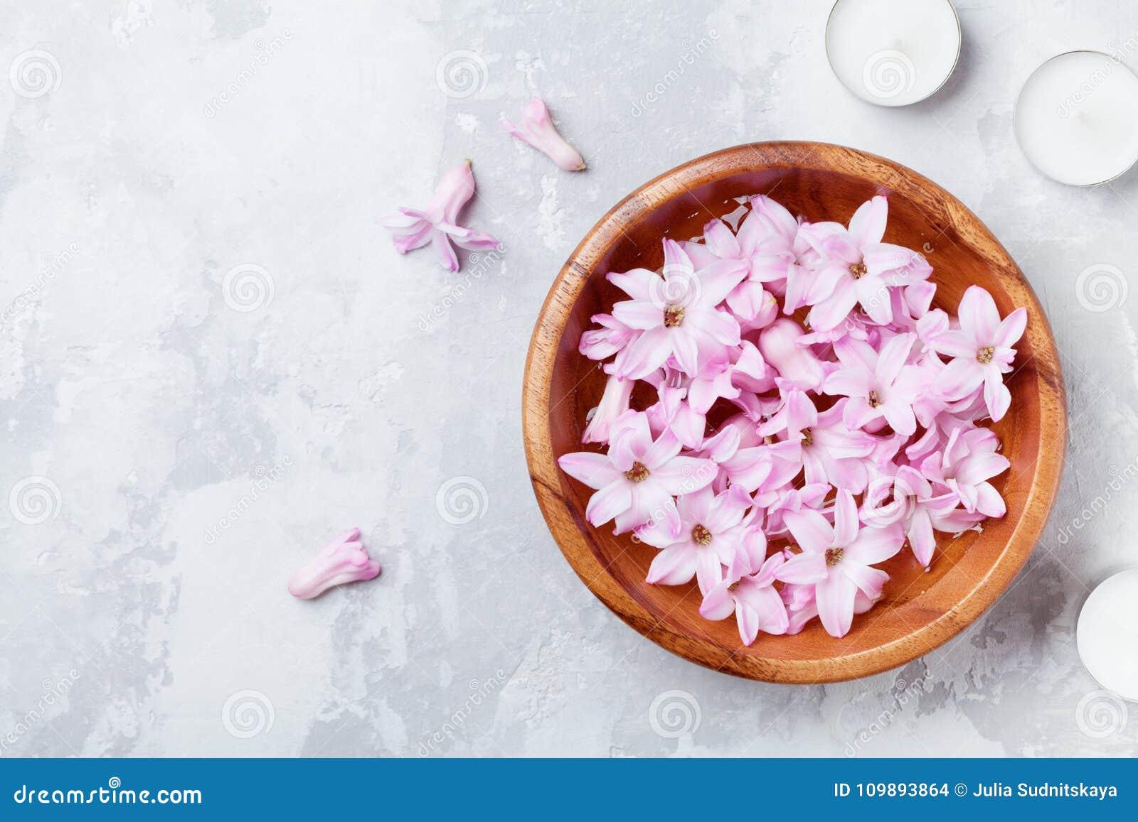 Schönheit, Badekurort und Wellnesszusammensetzung von parfümierten rosa Blumen wässern in der hölzernen Schüssel und in den Kerze