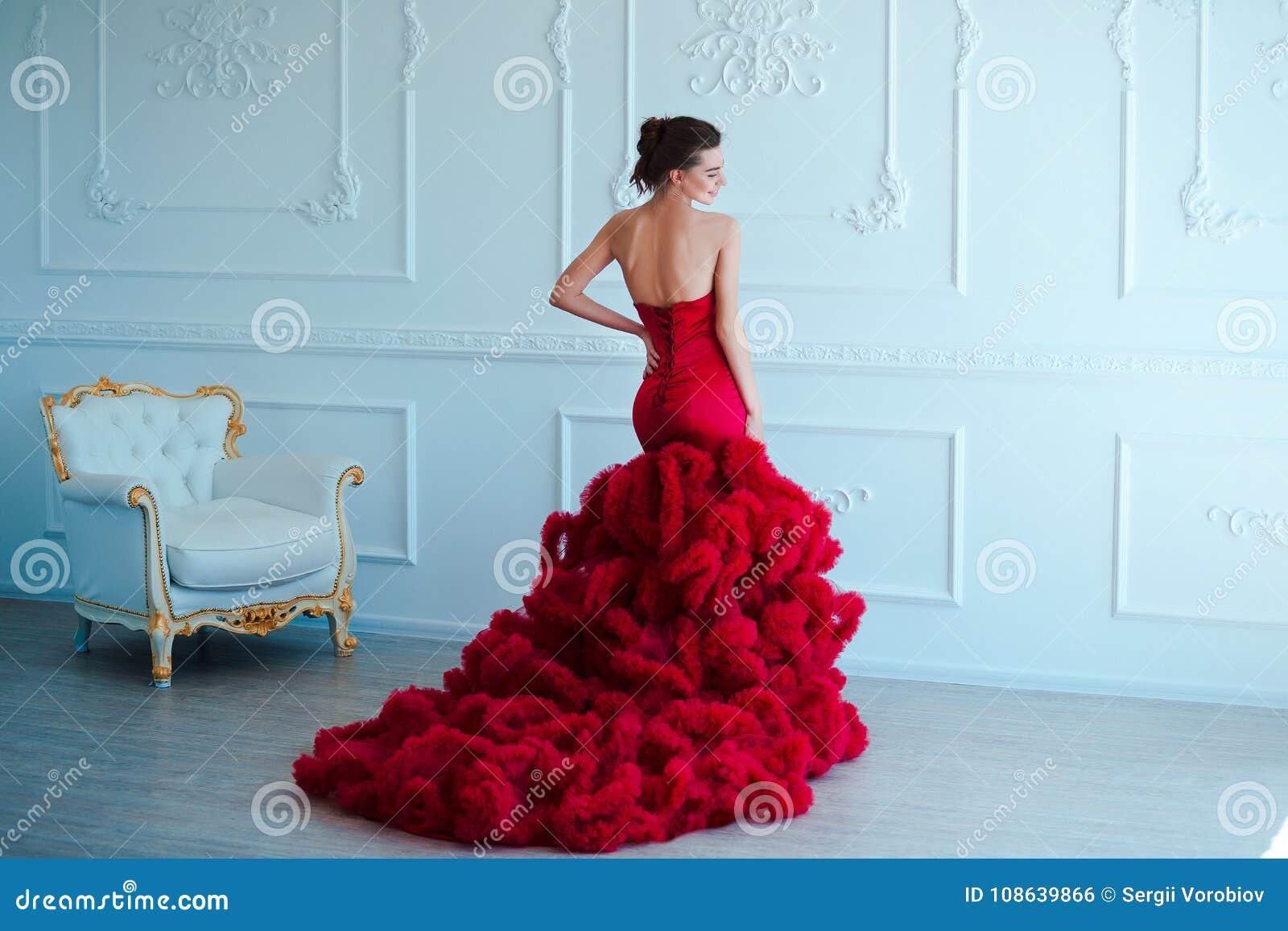 Schönheit Brunette-Modellfrau, wenn rotes Kleid geglättet wird Luxusmake-up und Frisur der schönen Mode Verlockendes Mädchen