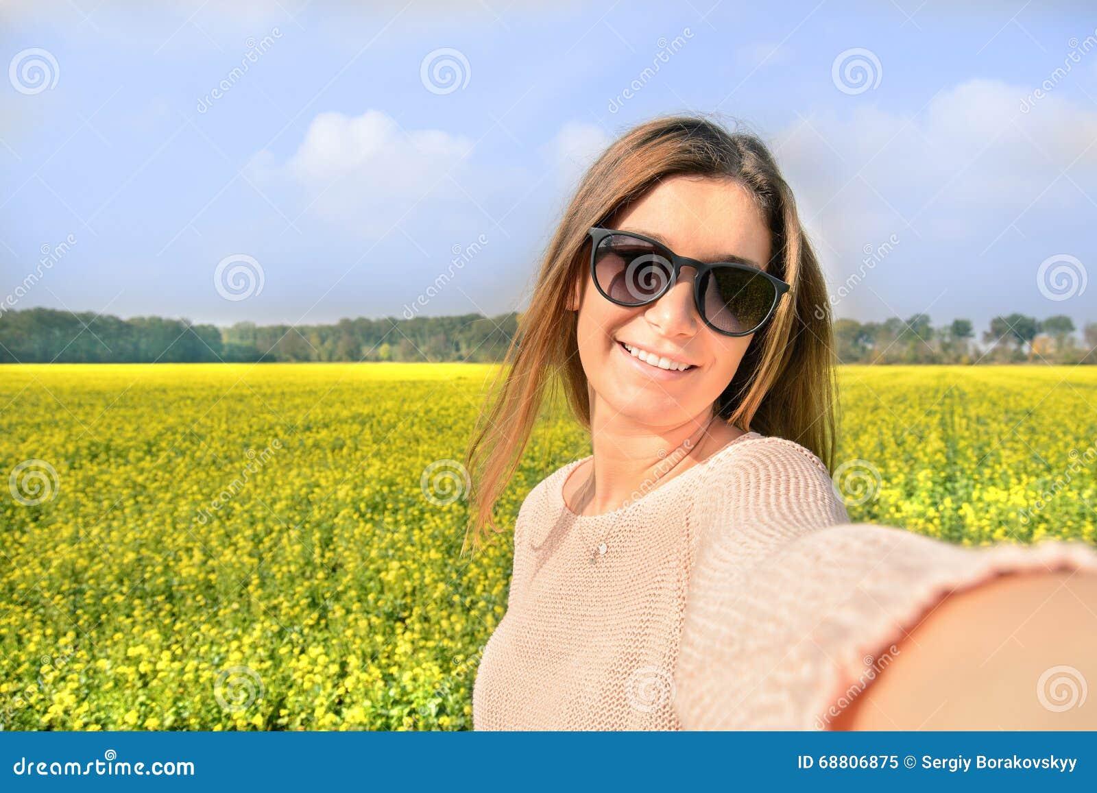 Schönheit, die selfie Foto von auf dem gelben Gebiet mit Naturhintergrund macht Schließen Sie herauf Portrait einer jungen Frau