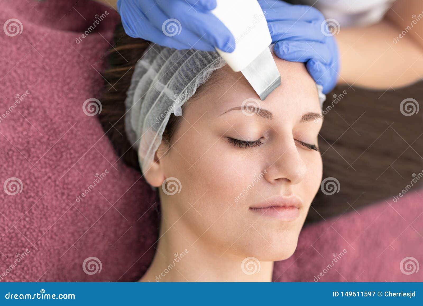 Schönheit, die Ultraschallhohlraumbildungs-Gesichtsschale im Schönheitsbadekurortsalon empfängt