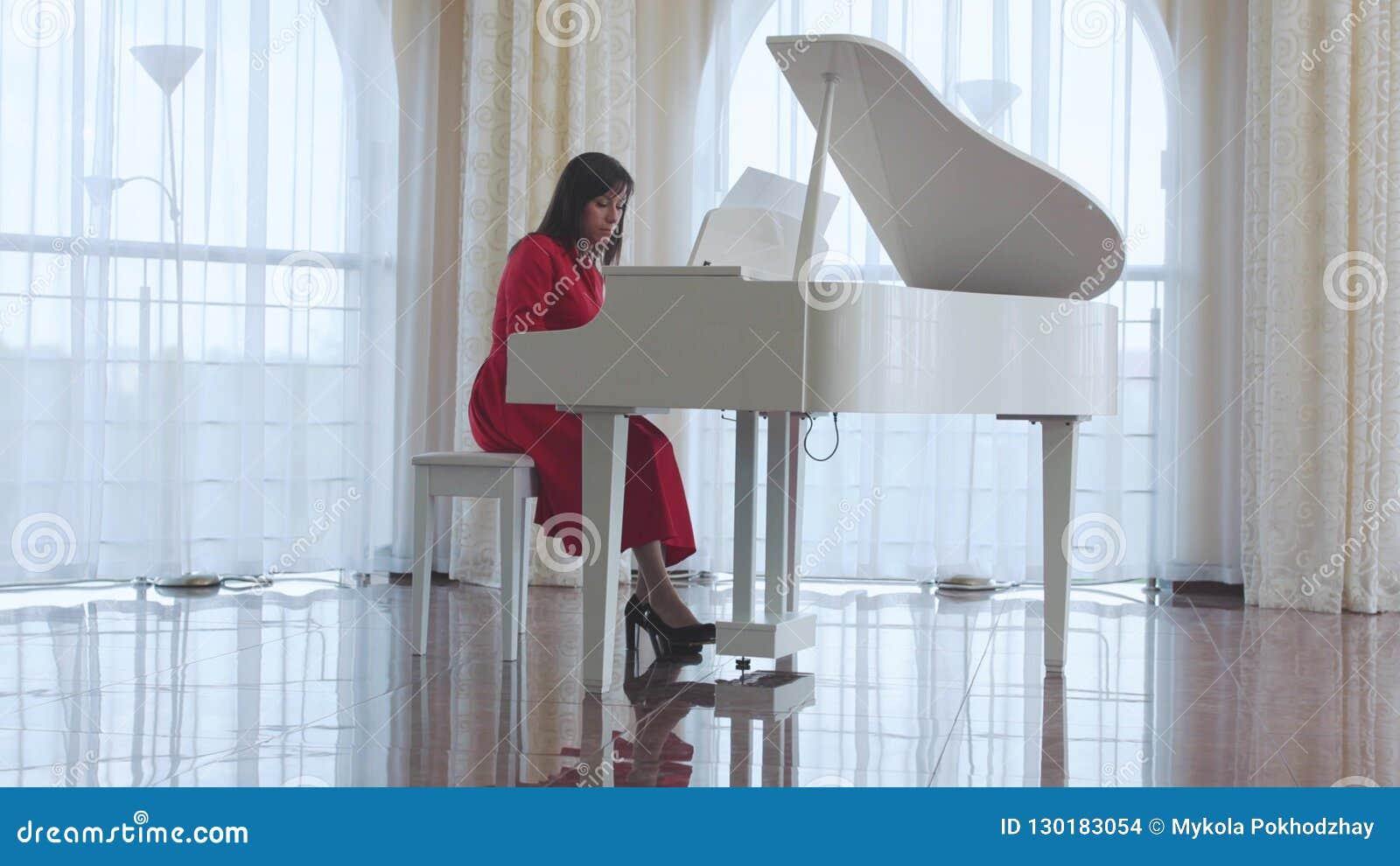 Schönheit spielt ein weißes Klavier