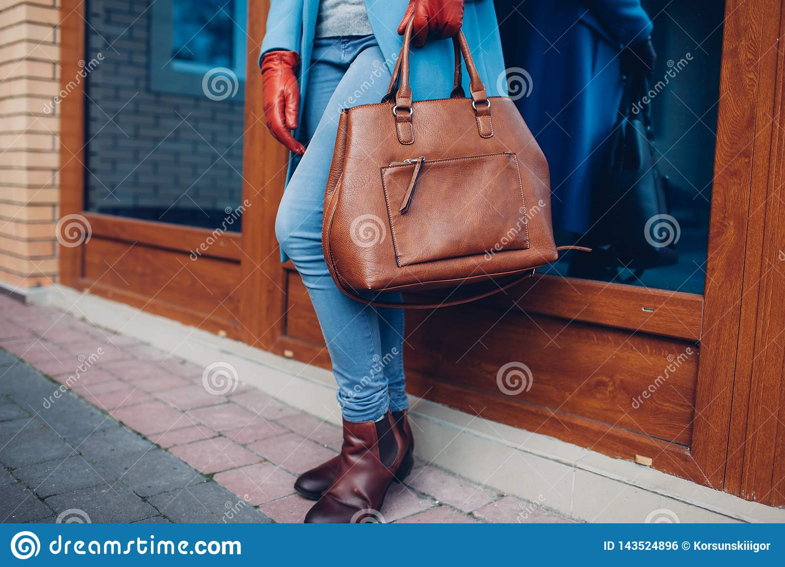 Schönheit und Mode Stilvoller tragender Mantel und Handschuhe der modernen Frau, braune Taschenhandtasche halten