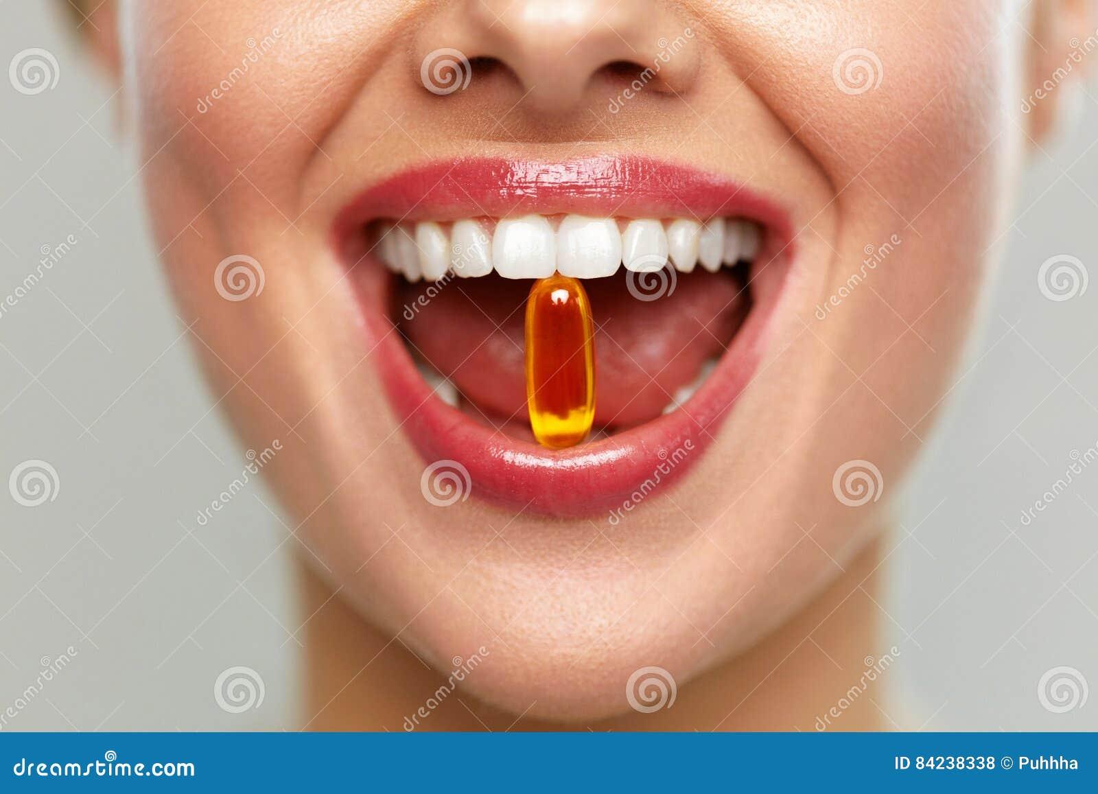 Schönheits-Mund mit Pille in den Zähnen Mädchen, das Vitamine nimmt