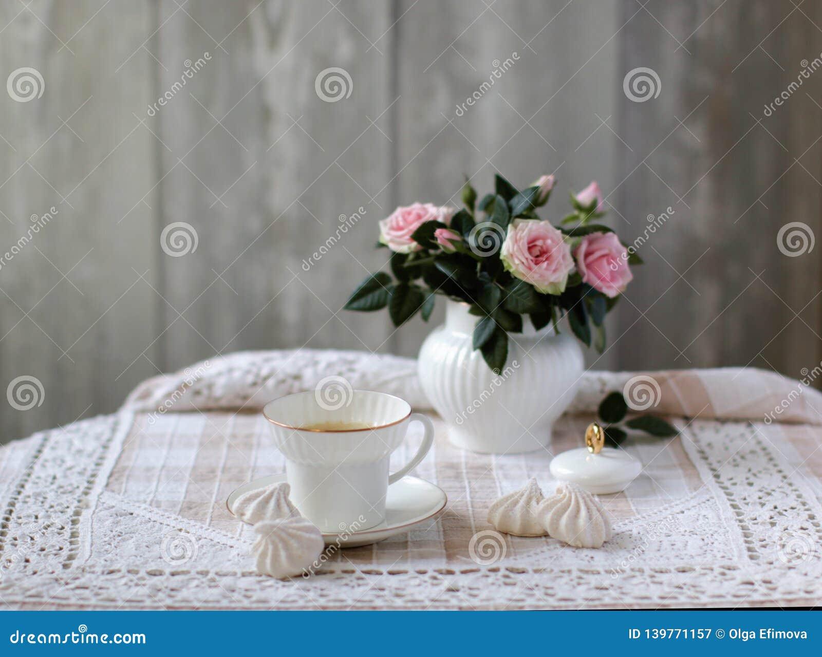 Schönheitsblumenstrauß von Rosen in der weißen Porzellanzuckerschüssel, Porzellanteeschale, Weinleseart, Blumenszene