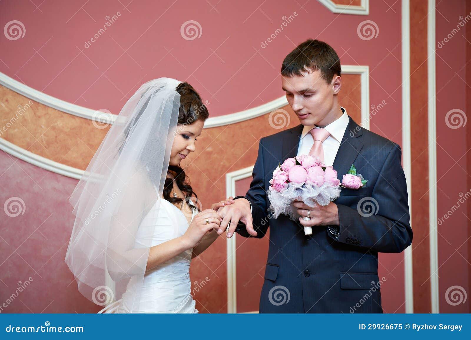 Schönheitsbraut trägt Ehering auf Finger des eleganten Bräutigams