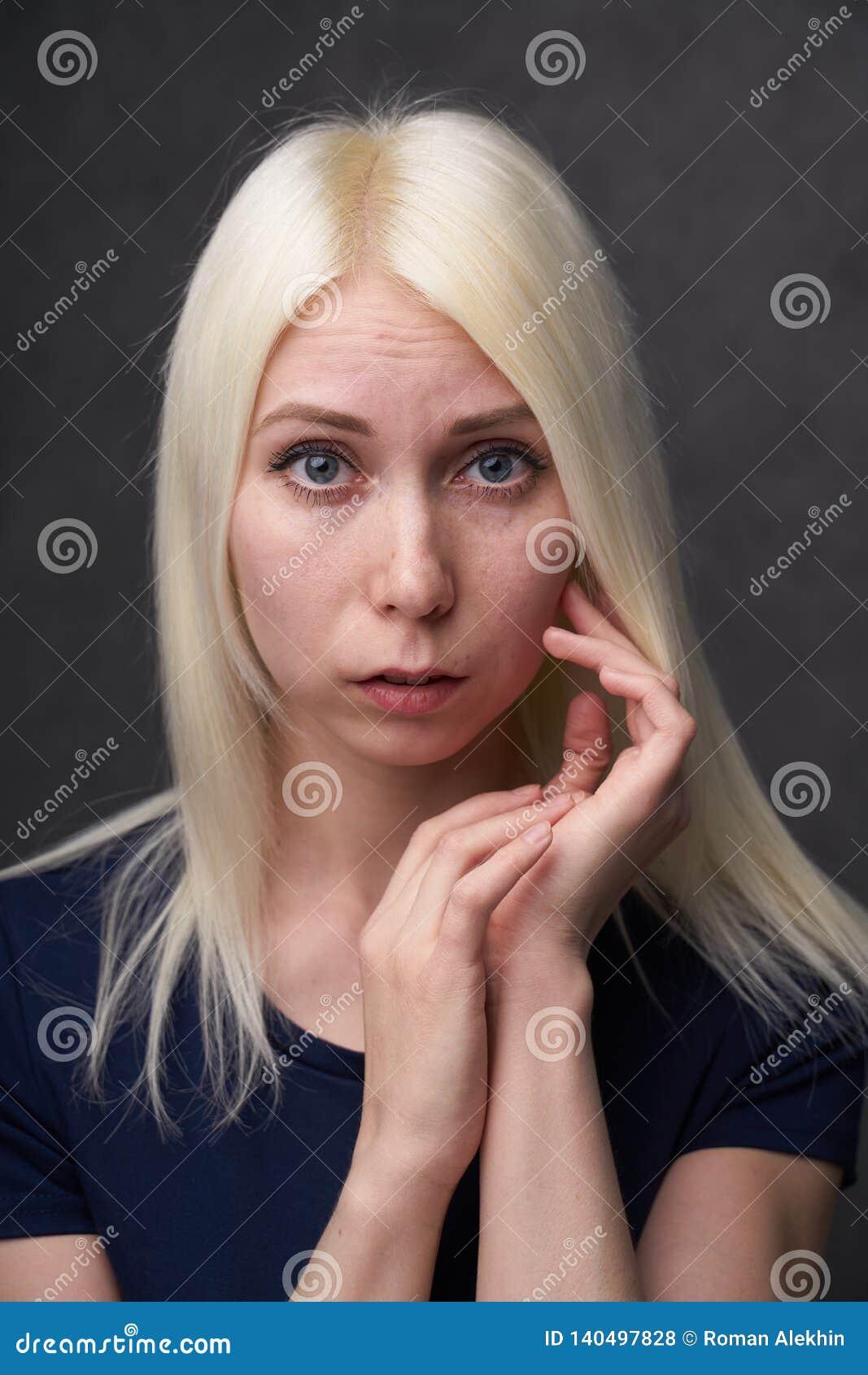 Schönheitsfrau blond in der schwarzen zufälligen Kleidung auf grauem Hintergrund
