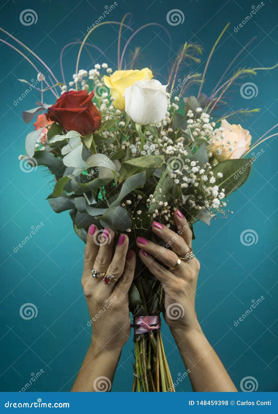Schönheitshände halten einen großen Blumenstrauß von Rosen