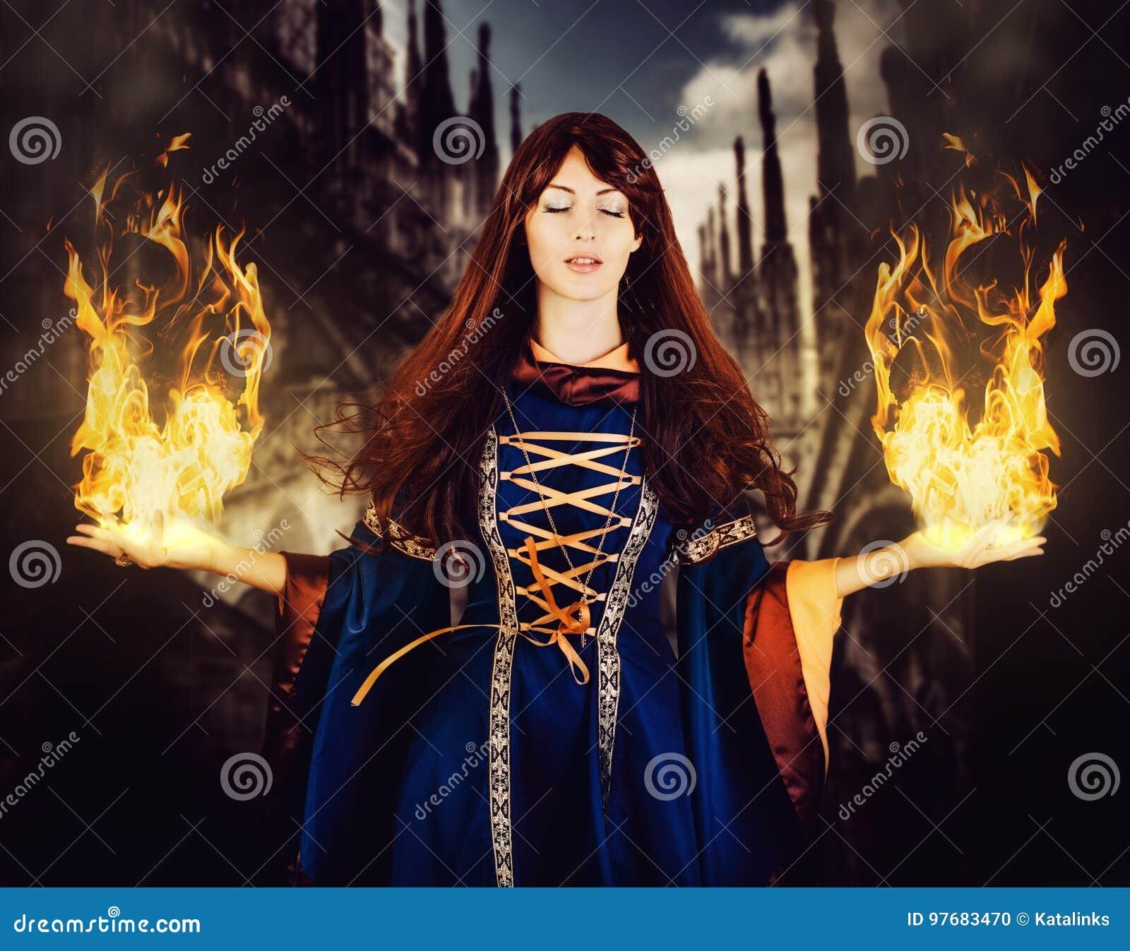 Schönheitshexe im mittelalterlichen Kleid der Fantasie Feuermagie