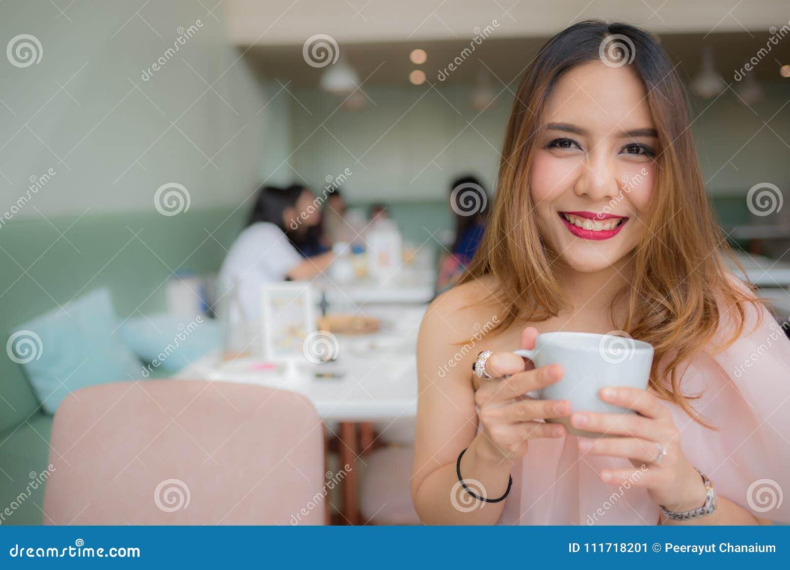Schönheitslächeln und Halten eines Tasse Kaffees in ihrer Hand an der Kaffeestube