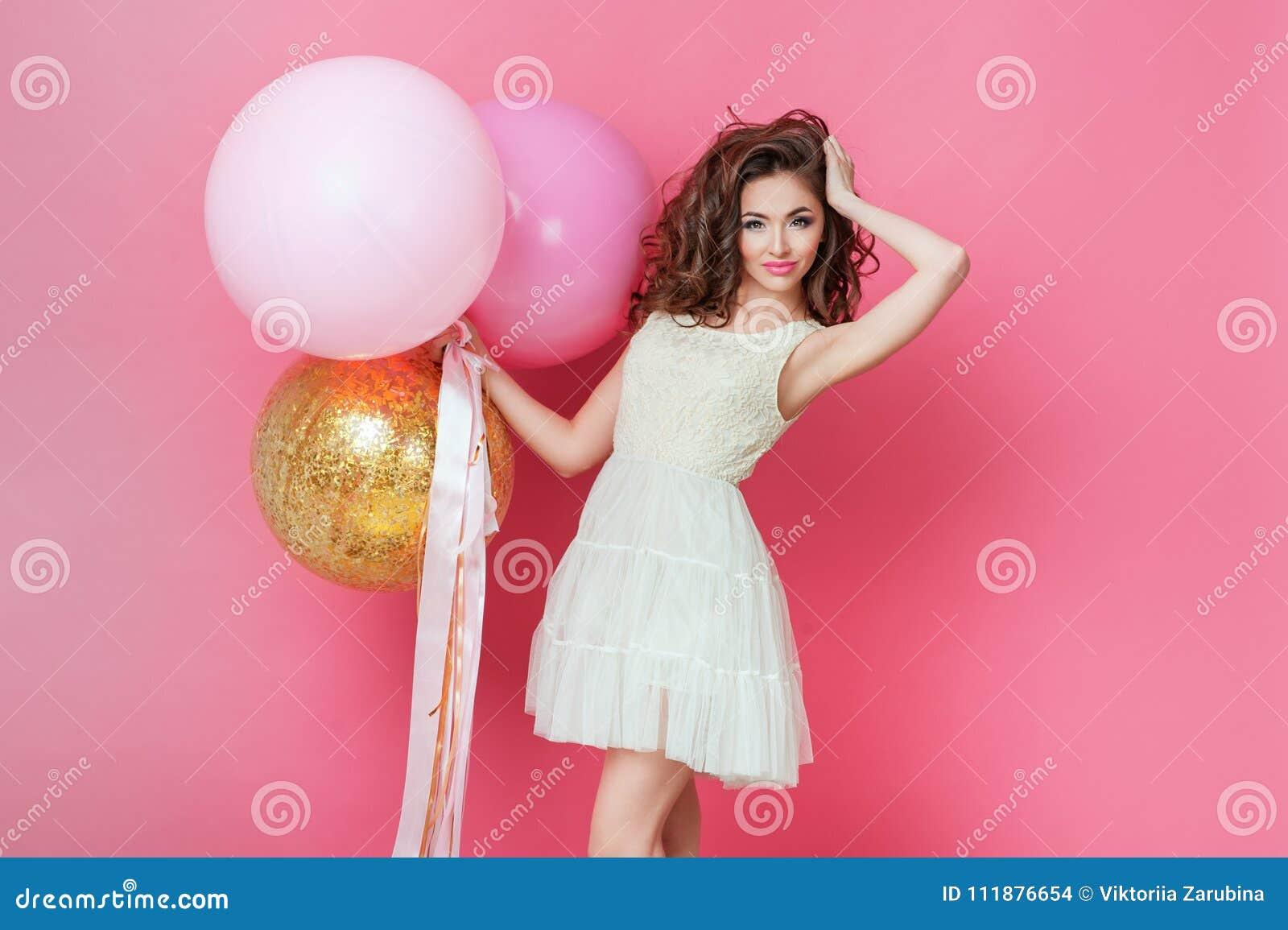 Schönheitsmädchen mit bunten Luftballonen lachend über rosa Hintergrund Schöne glückliche junge Frau auf Geburtstagsurlaubsparty