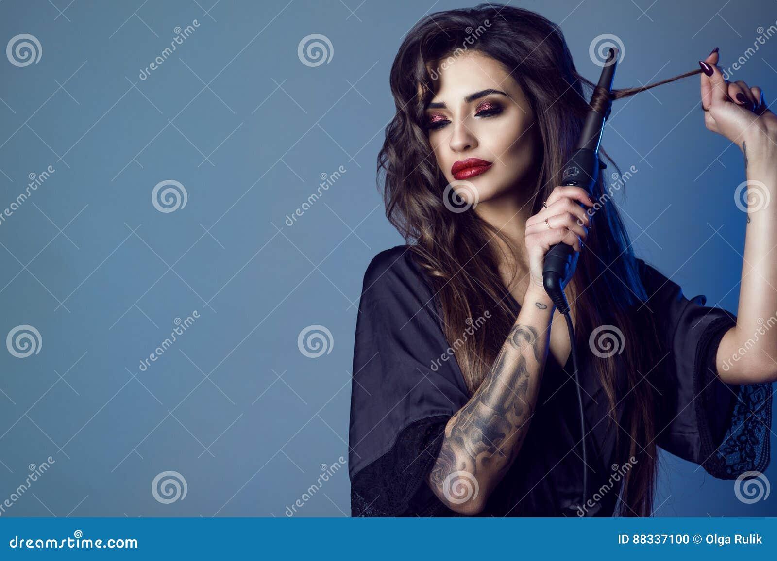 Schönheitsporträt des jungen herrlichen Modells im schwarzen silk peignoir mit dem langen Haar und provozierenden dem Make-up, di