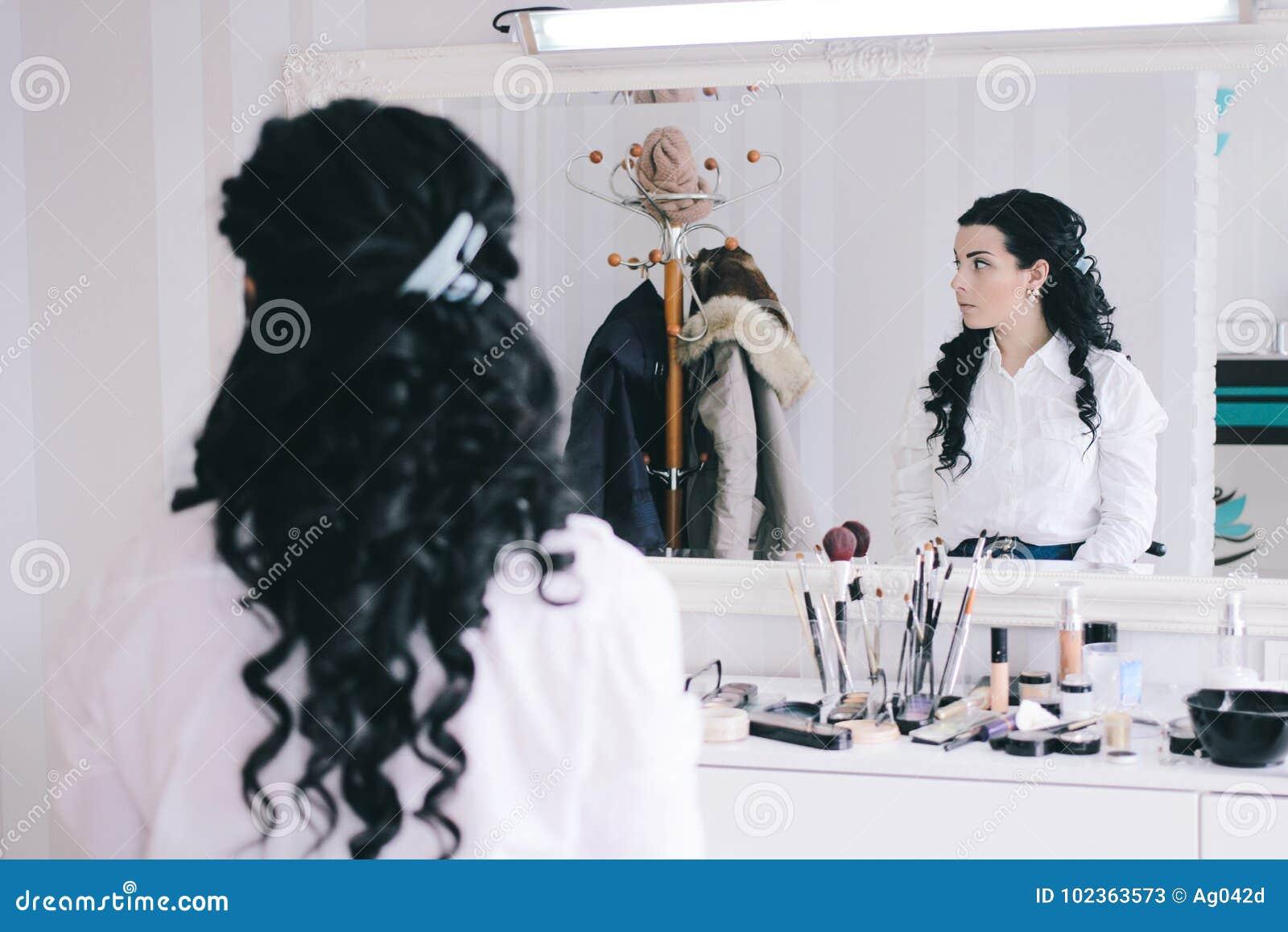 Schönheitssalon, Mädchen mit dem langen schwarzen Haar sitzt am Spiegel im Schönheitsstudio
