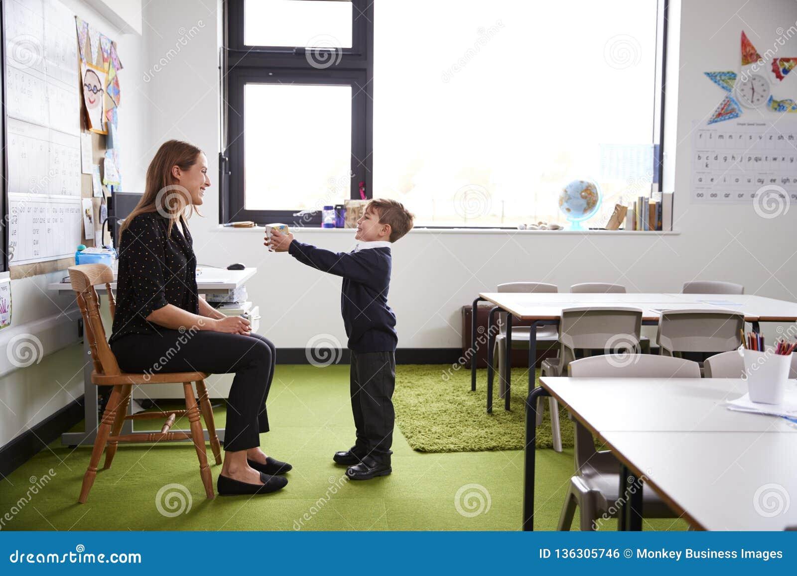 Schüler an der Grundschule, die ein Geschenk seinem weiblichen Lehrer in einem Klassenzimmer, Seitenansicht in voller Länge darst