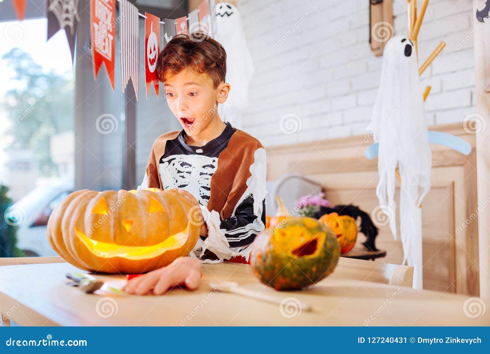 Schüler, der skeleton Kostüm für Halloween steht nahen Kürbis trägt