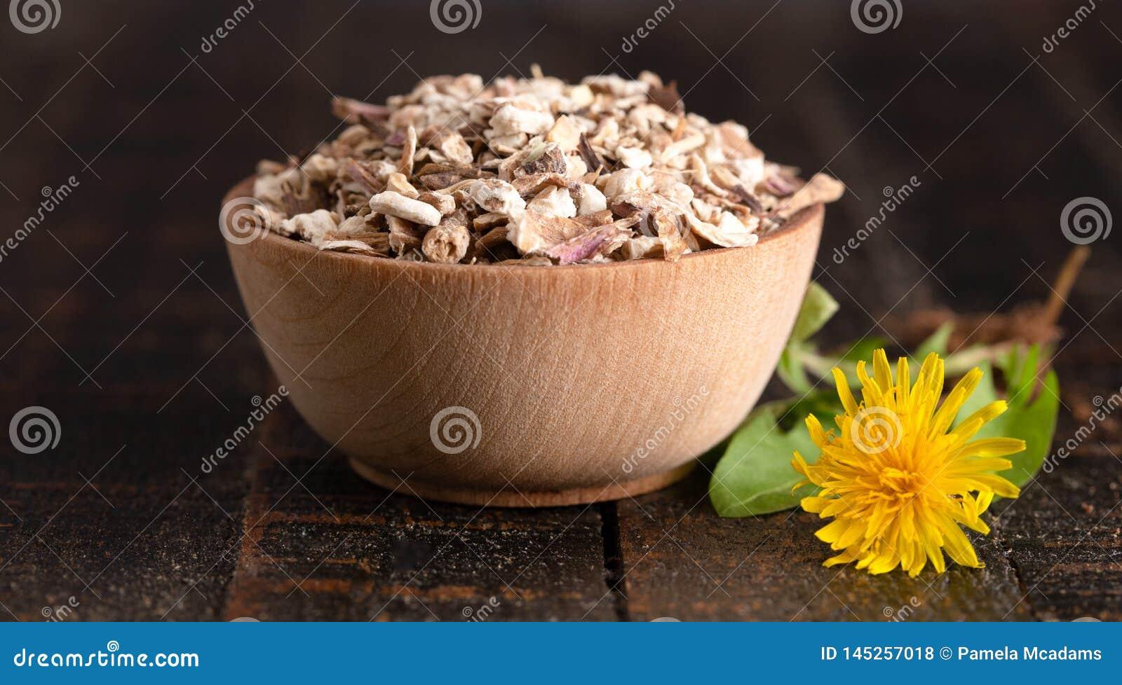 Schüssel der entwässerten Löwenzahn-Wurzel auf einem rustikalen Holztisch