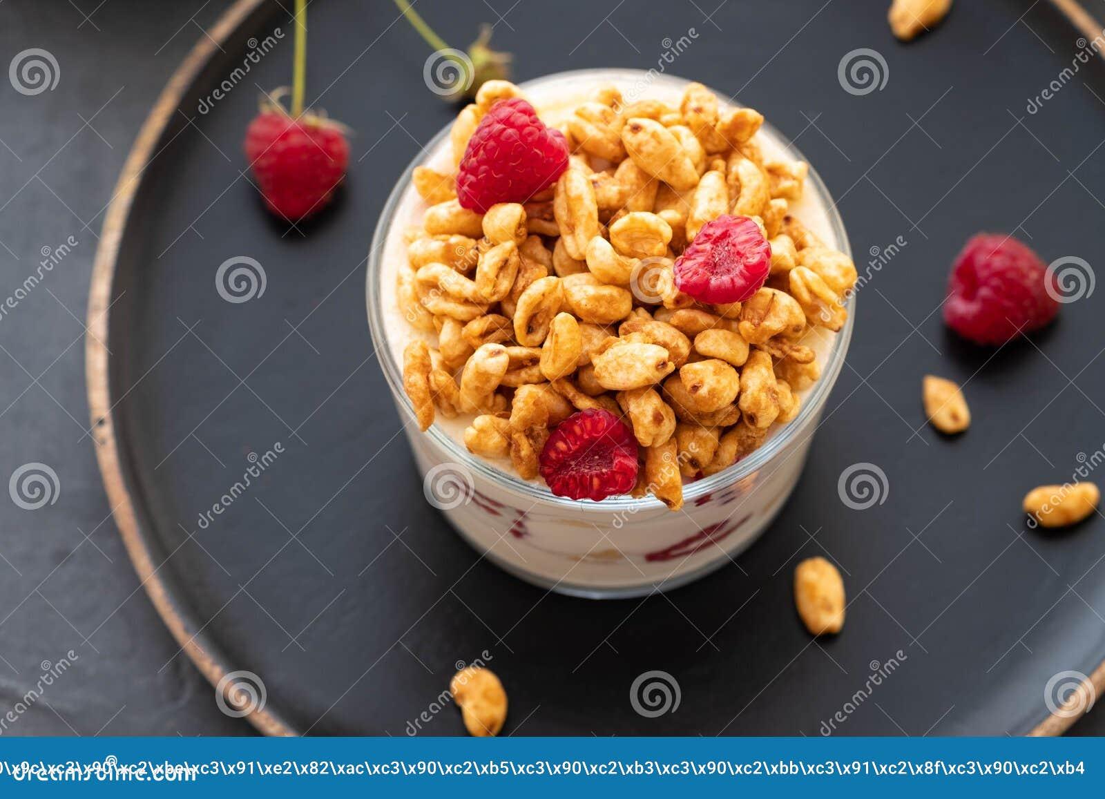 Schüssel Granola mit Jogurt und frischen Beeren auf schwarzem Hintergrund von der Draufsicht Gesunder Frühstück Kopienraum
