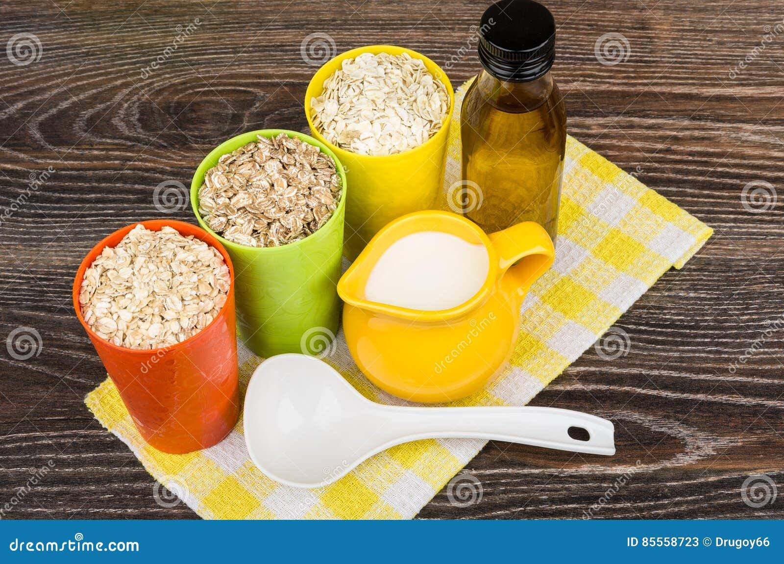 Schüssel und Schalen mit Hafer, Roggen, Gerstenflocken, Pflanzenöl