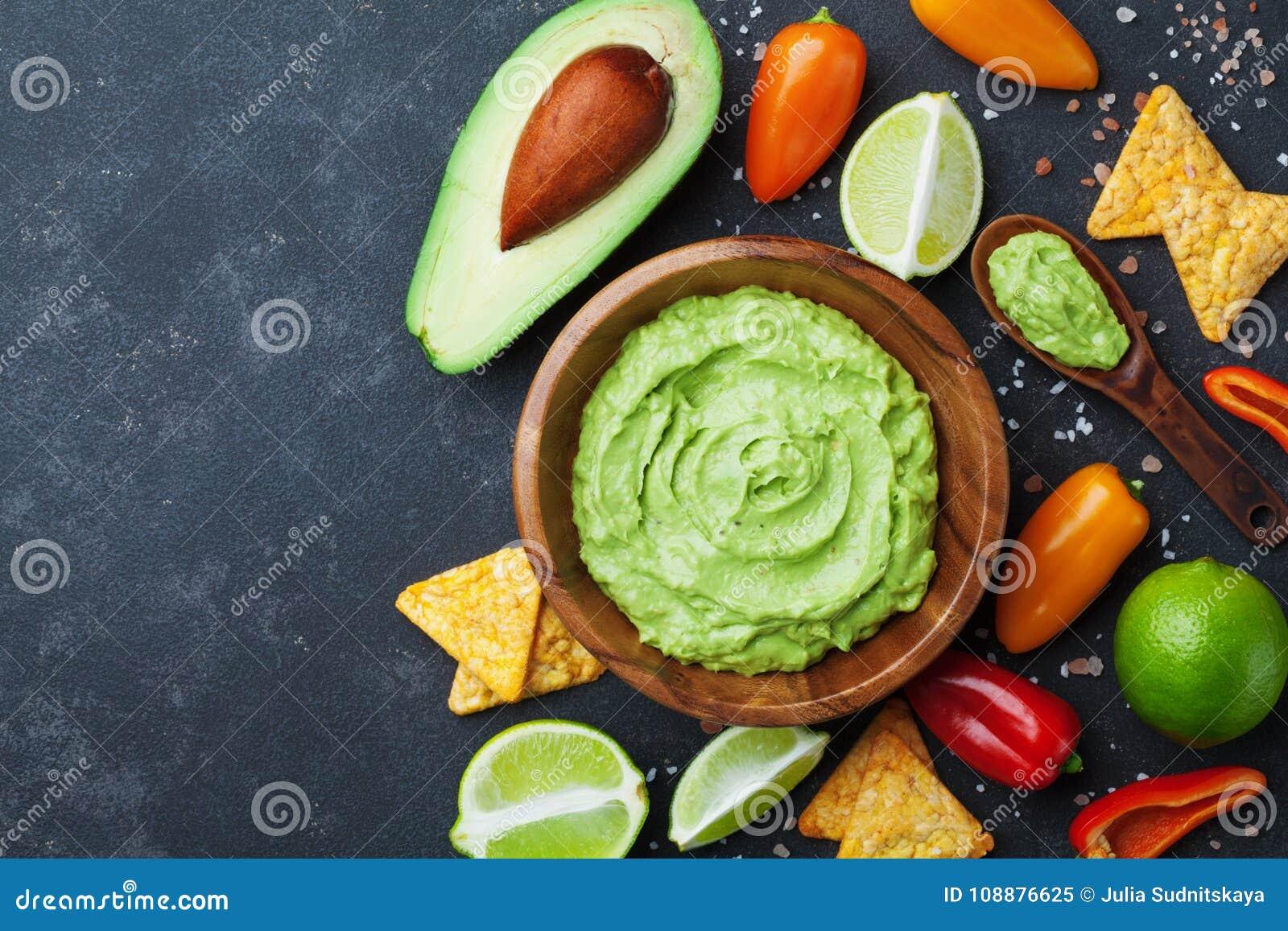 Schüsselguacamole mit Draufsicht der Avocado, des Kalkes und der Nachos Mexikanische Nahrung